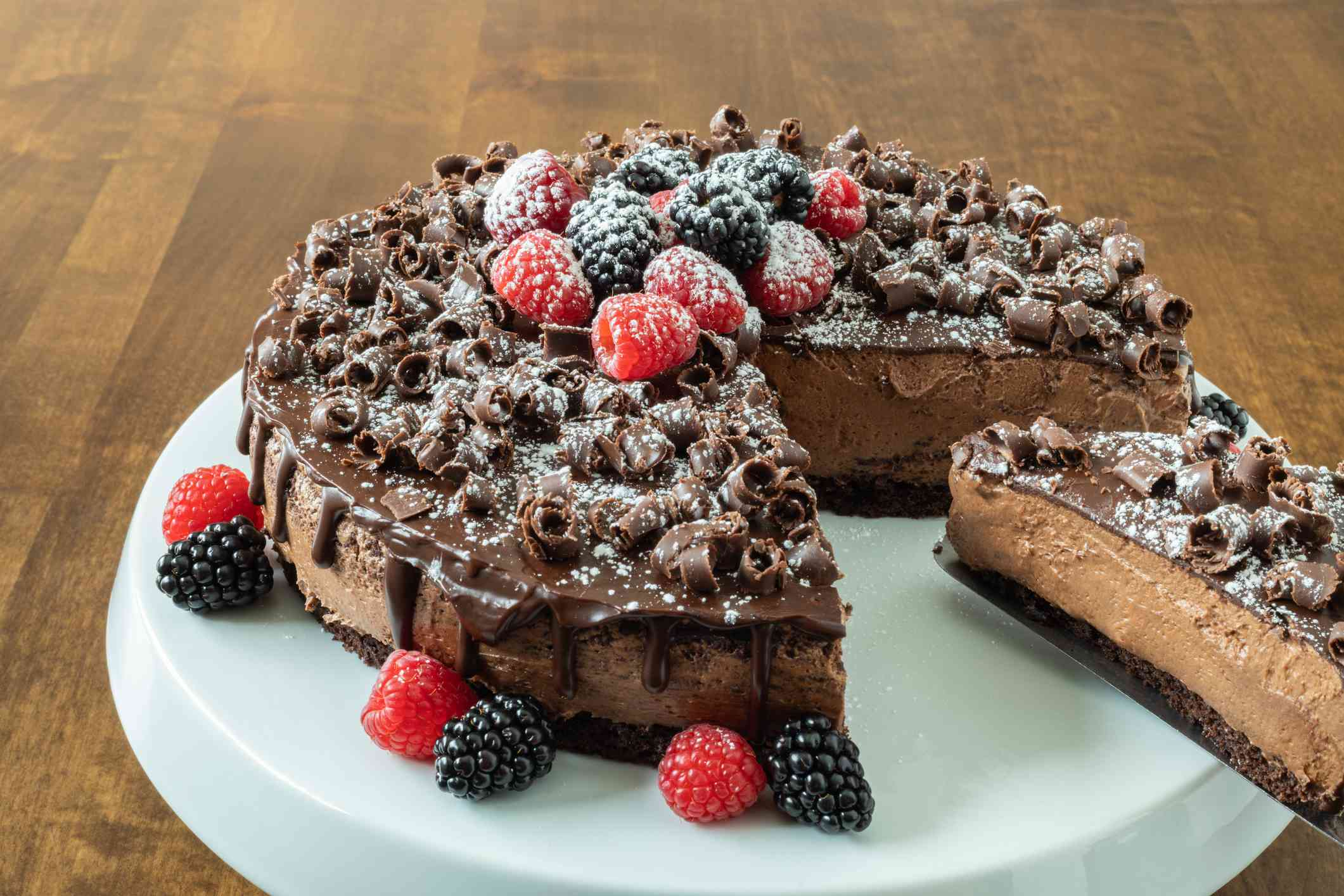 Chocolate mousse cake with chocolate ganache and topped with raspberries, blackberries and chocolate curls