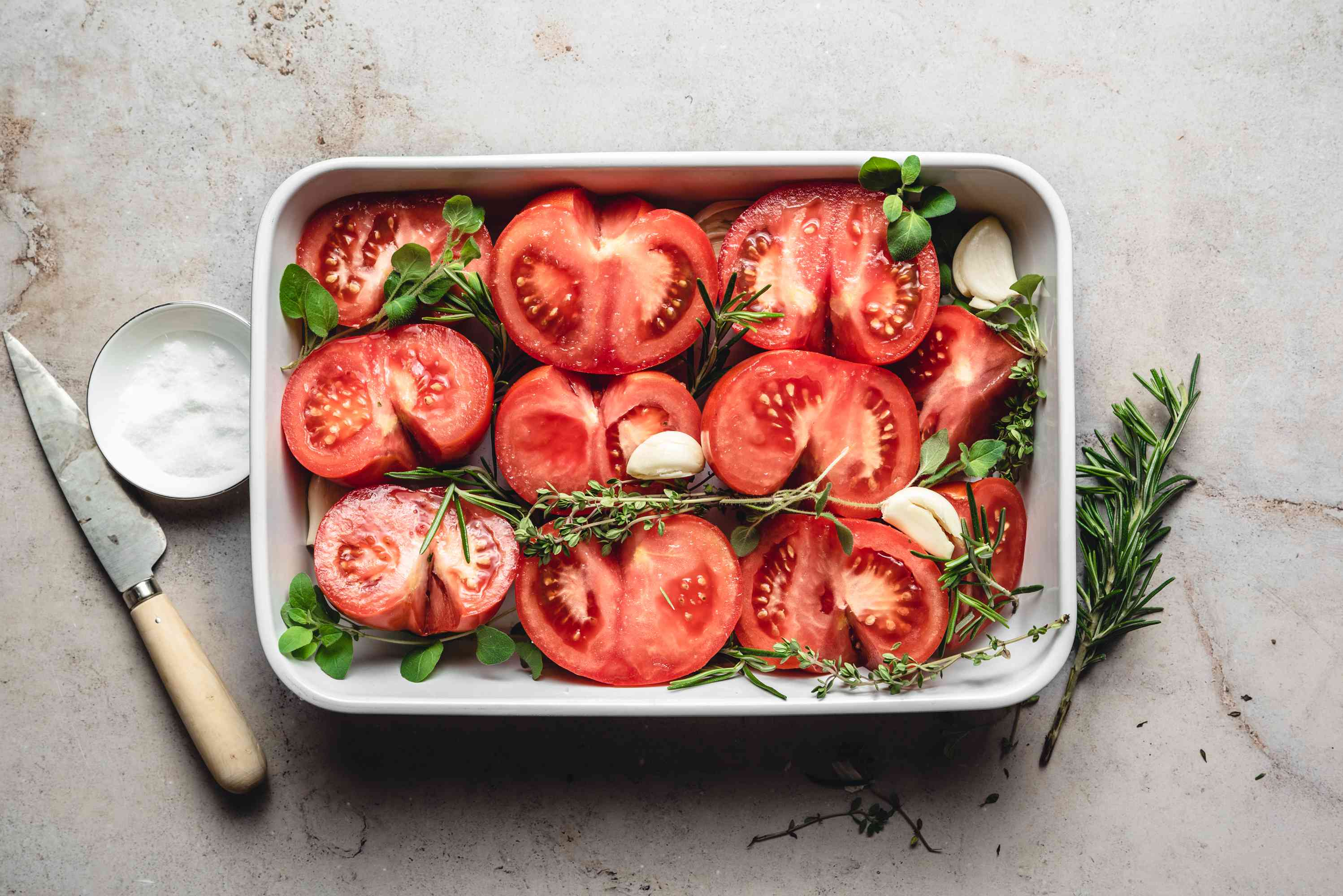 tomatoes with salt, herbs and garlic in a baking dish
