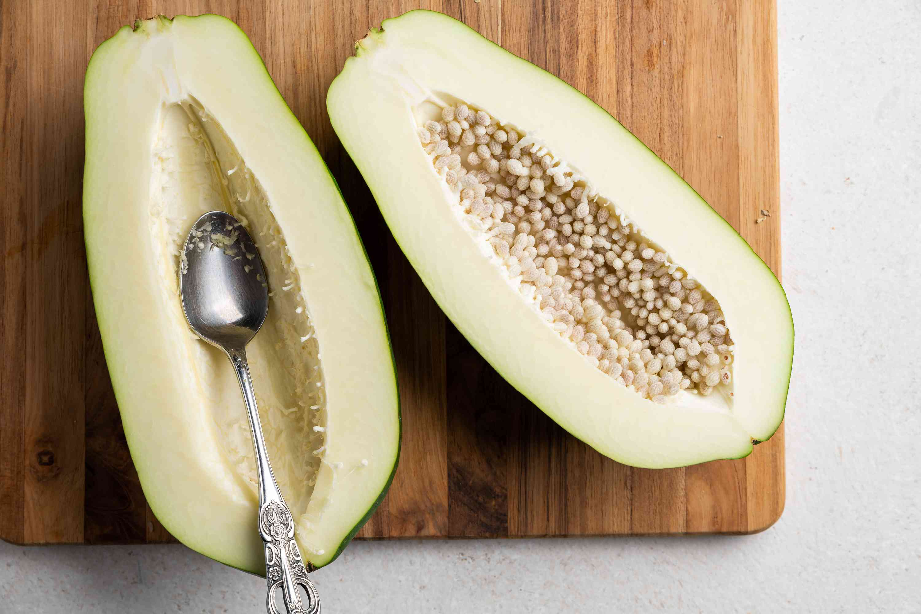 Split the green papaya vertically and scoop out the seeds with a spoon