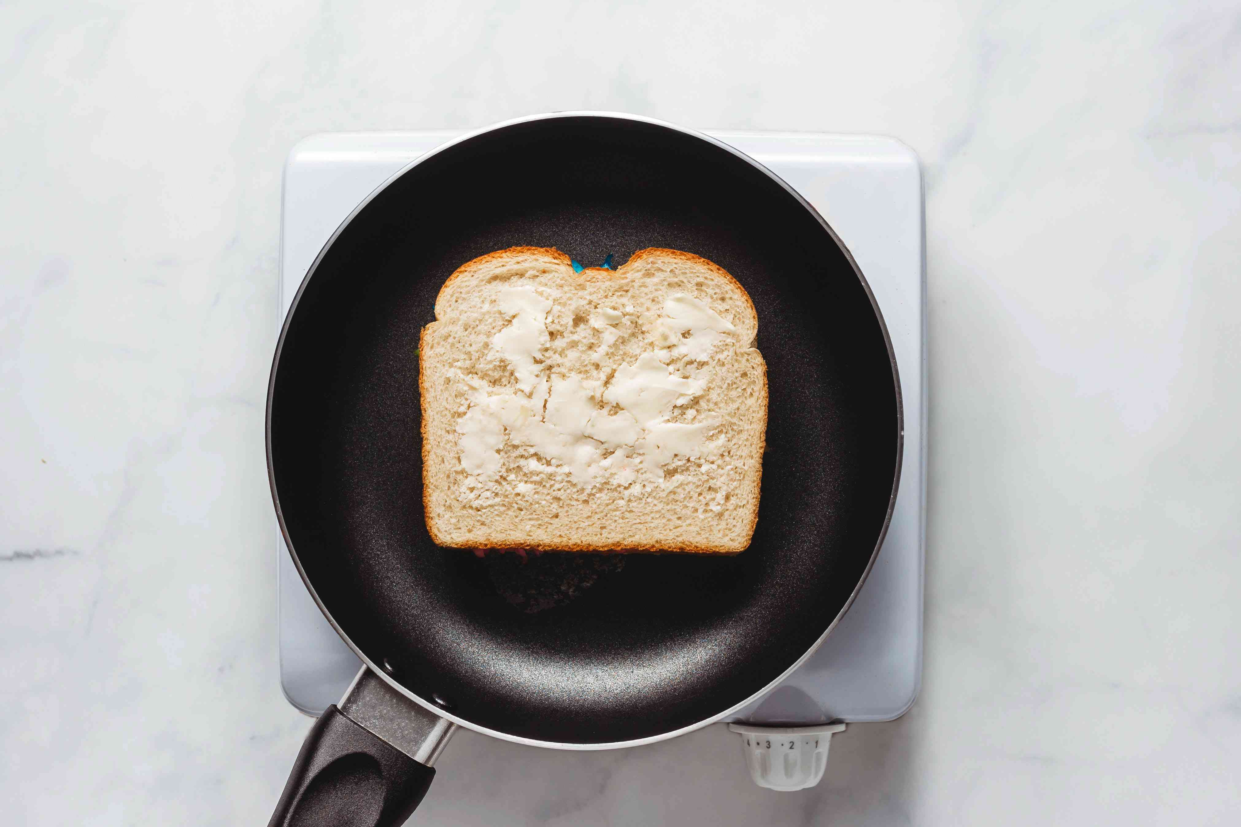grilled cheese in pan with butter being cooked