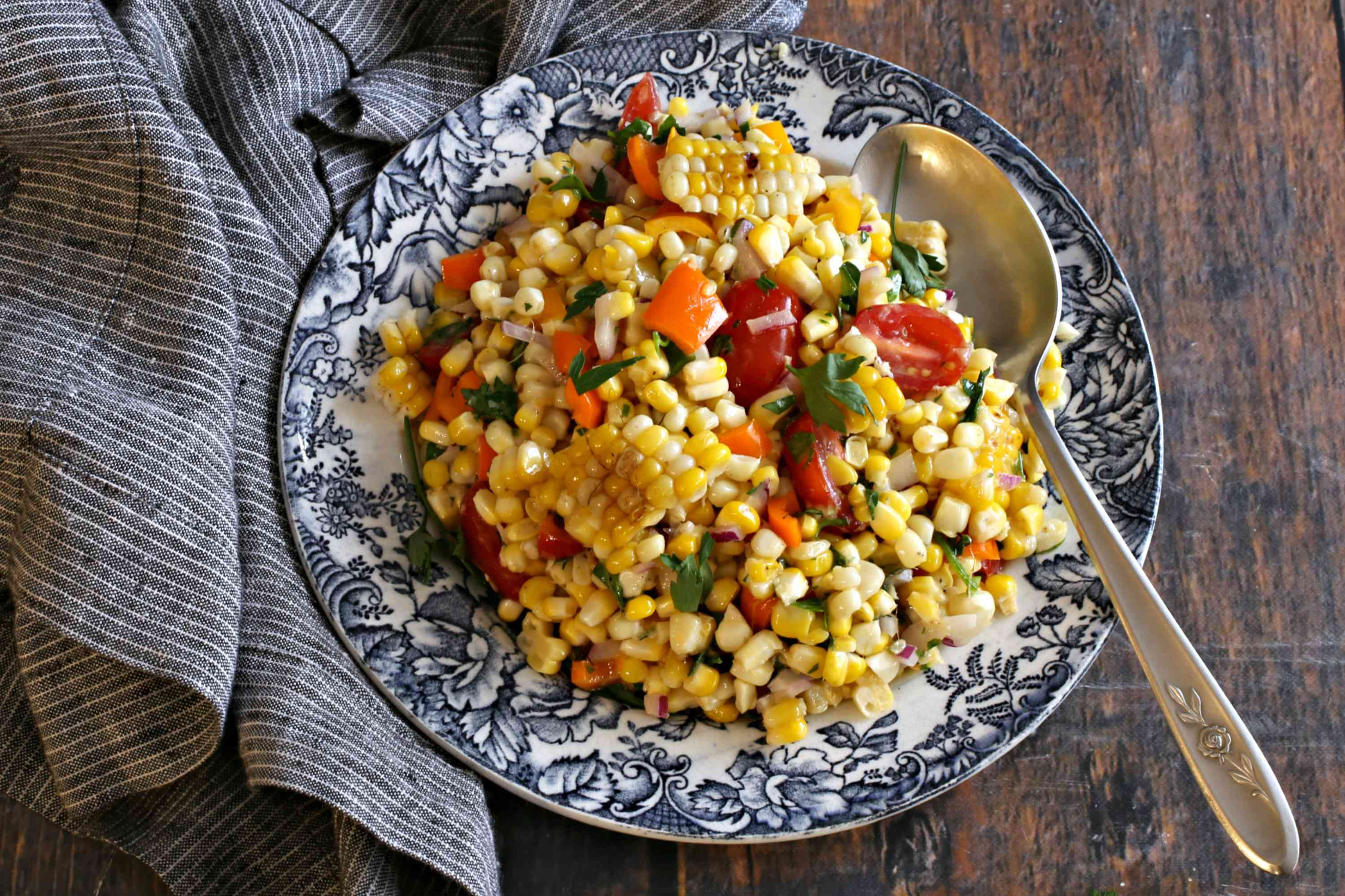 Grilled corn salad in a serving bowl with a spoon