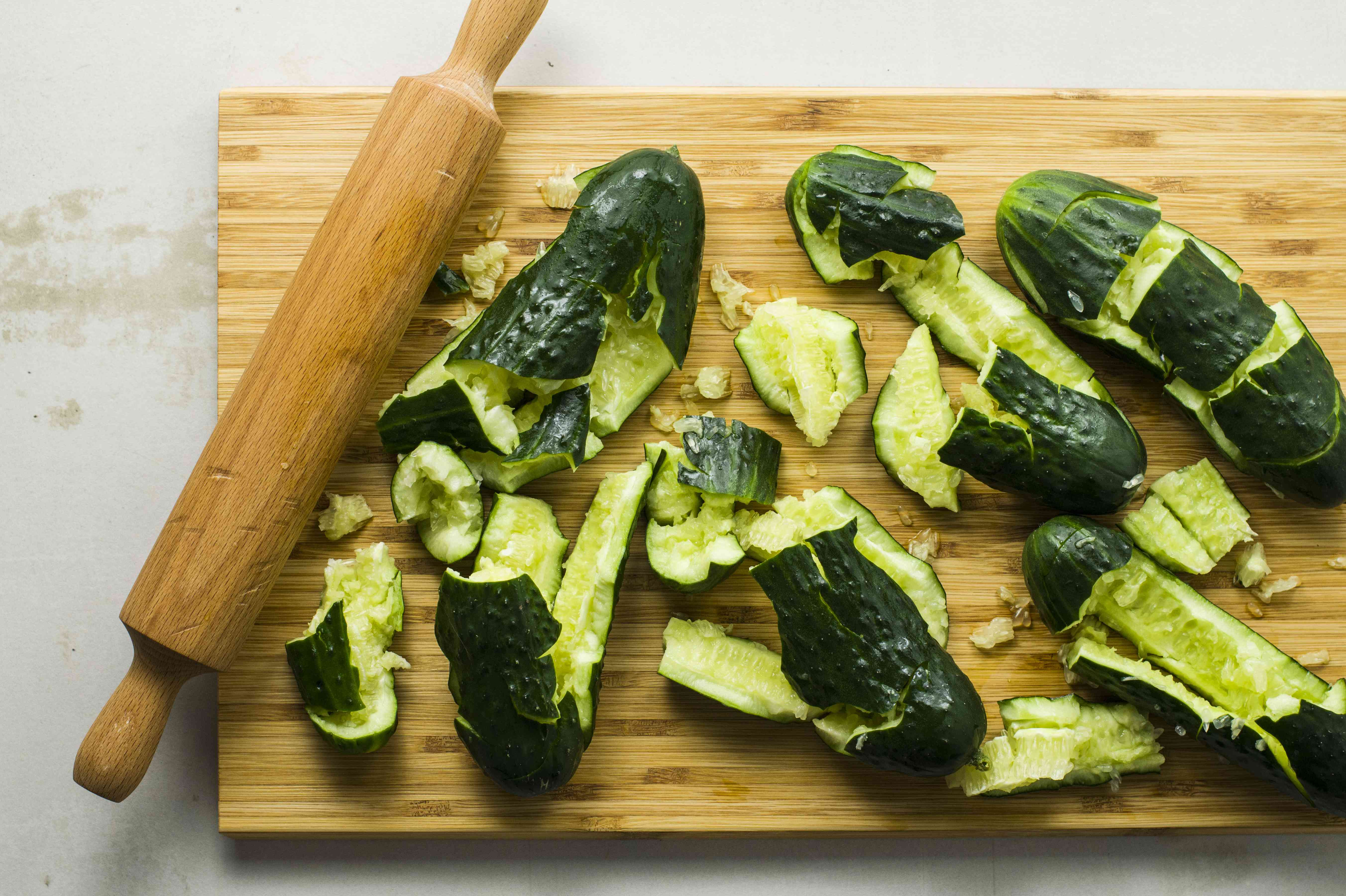 Cucumbers smashed on a cutting board by a rolling pin