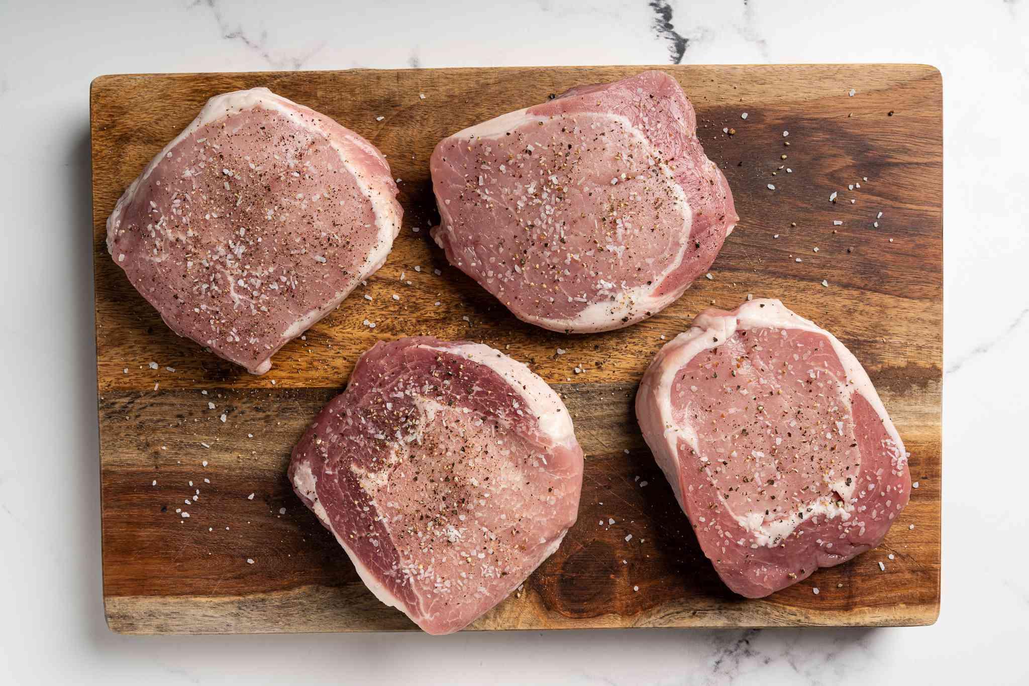season pork chops on the wood cutting board