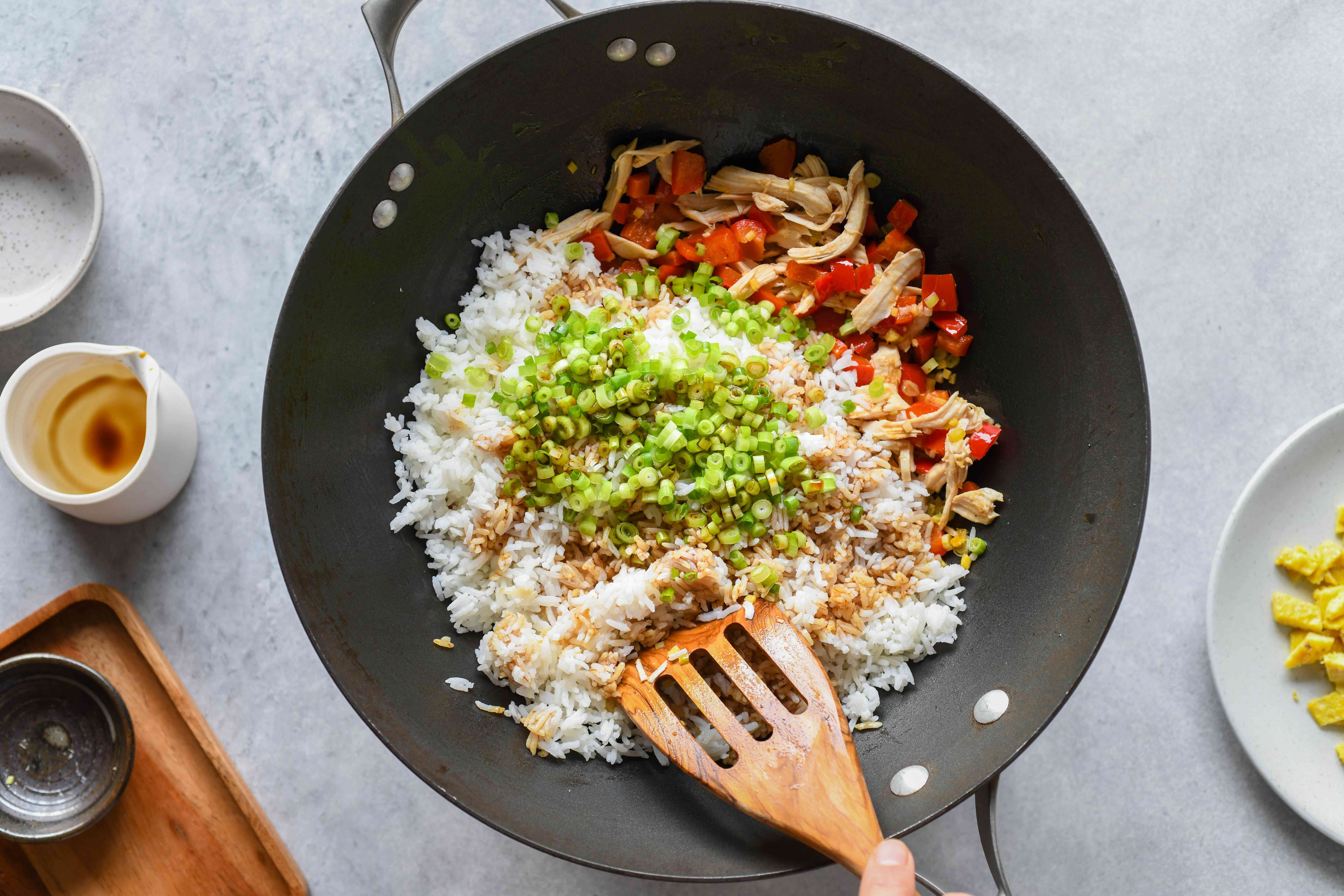 cooked rice, scallions, and soy sauce with peppers and chicken in a wok