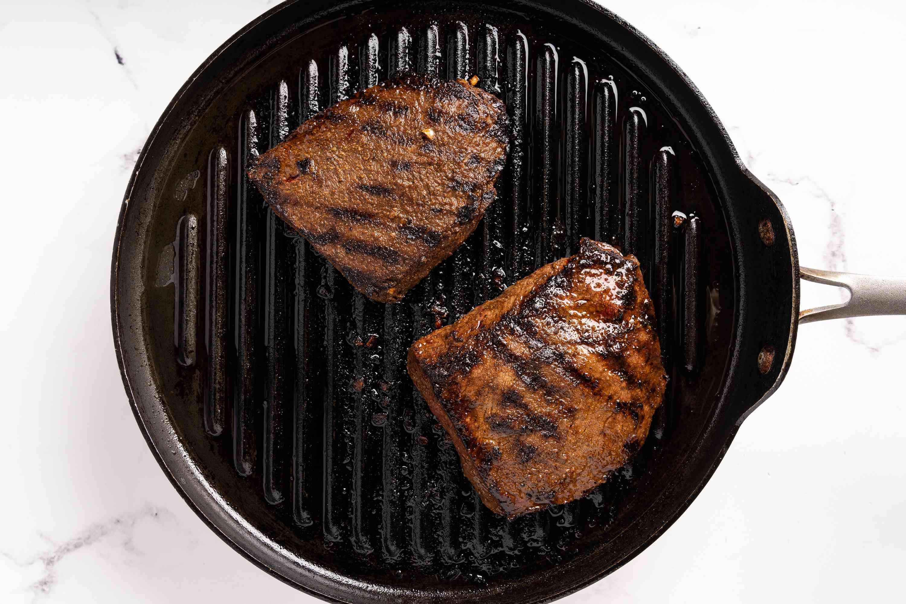 steaks cooking on a grill pan
