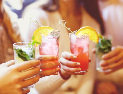 people holding cocktails at a party