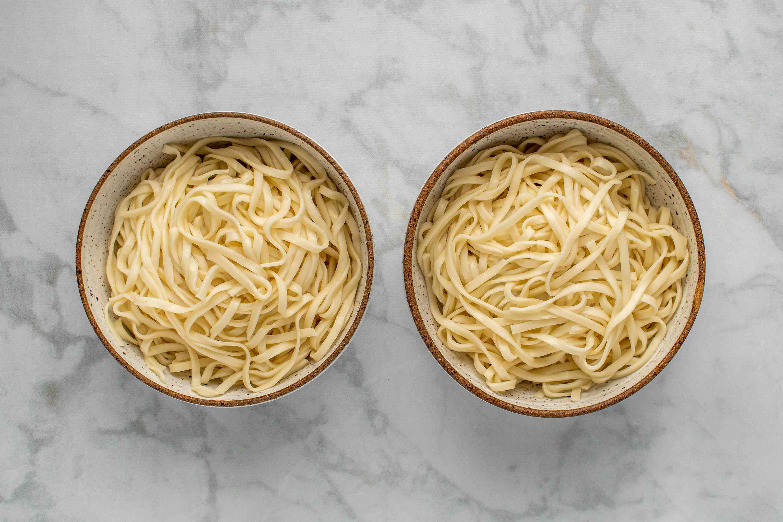 Divide the egg noodles between two large bowls
