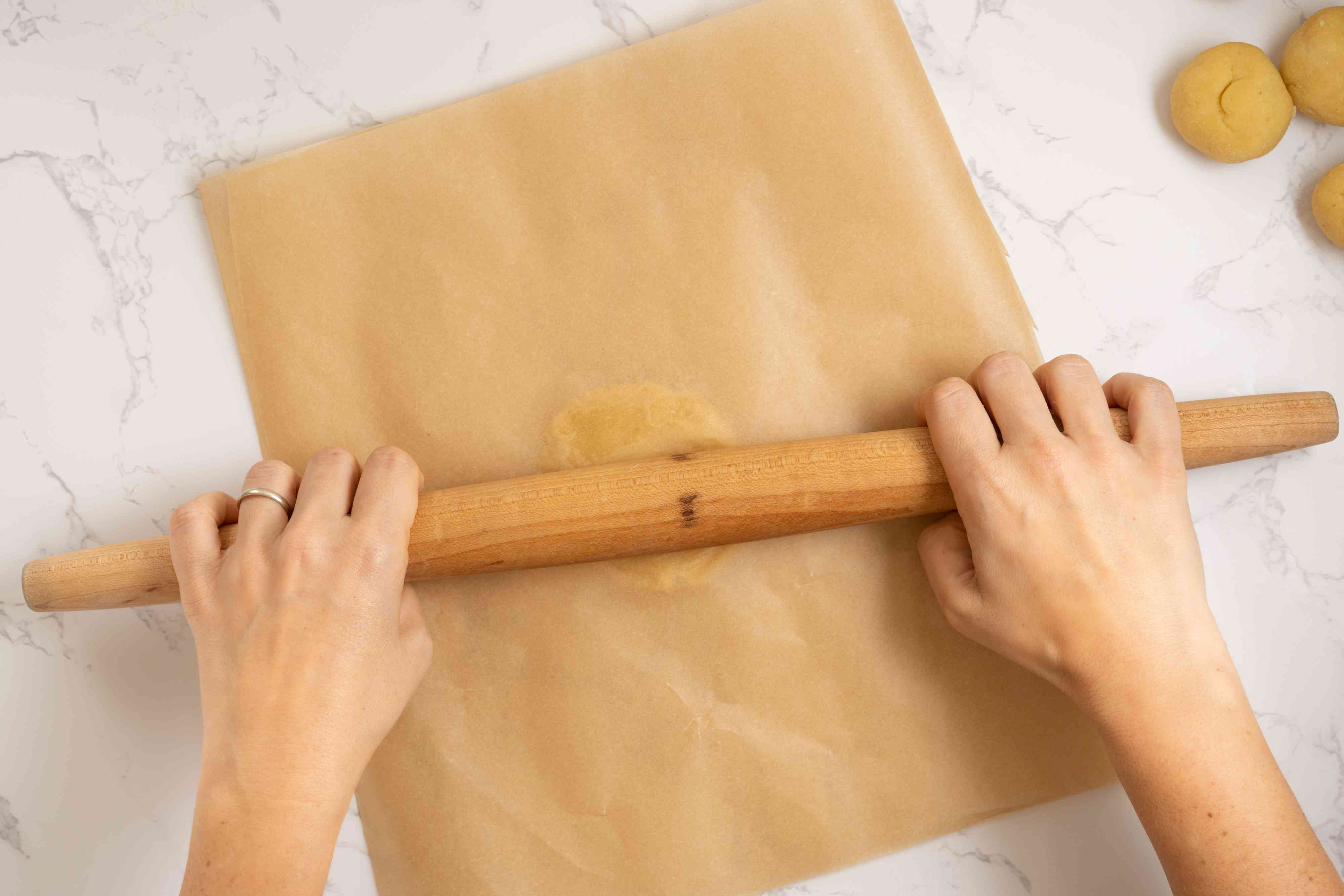 dough rolled out between parchment paper