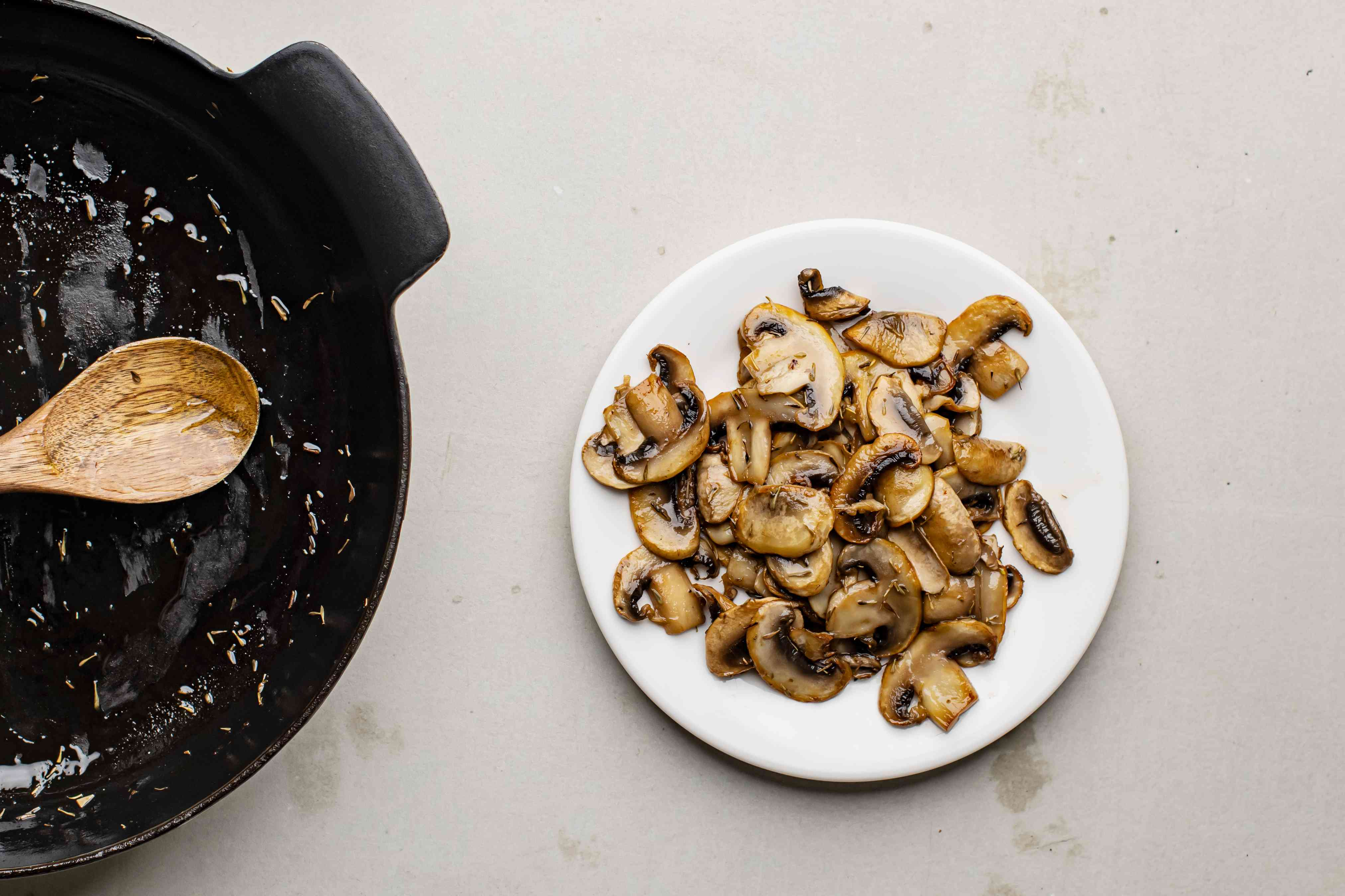 Cooked mushrooms on plate next to skillet