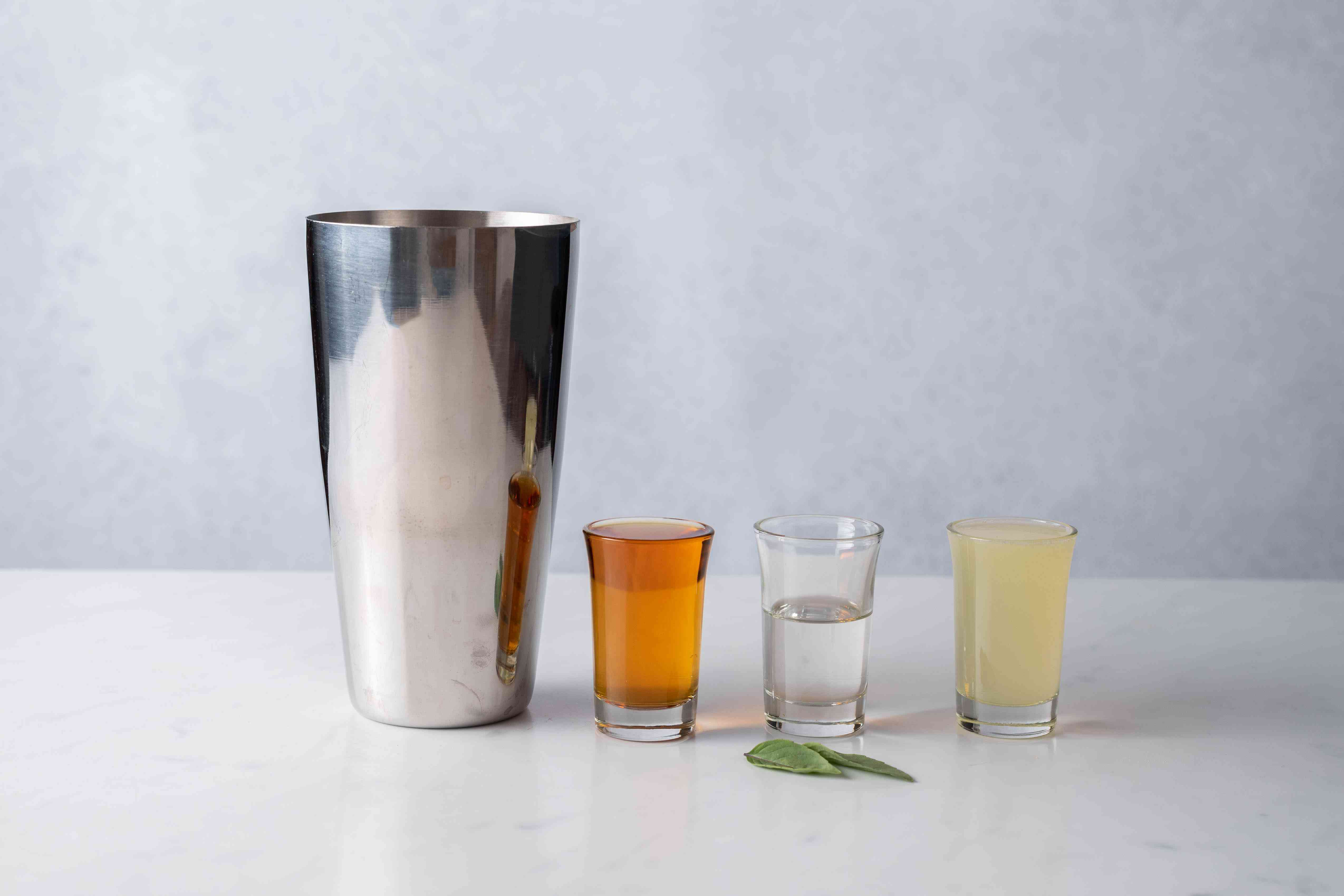 Mekhong, juice, syrup, and basil and a mixing glass