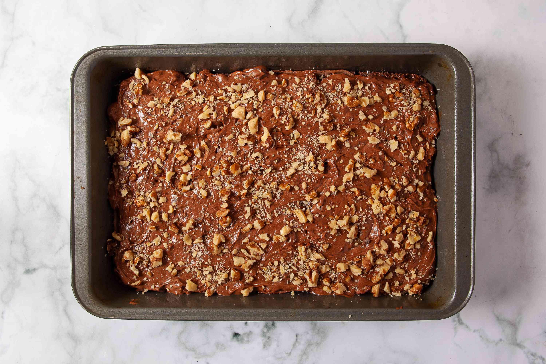 Walnuts sprinkled on top of brownie batter in a pan