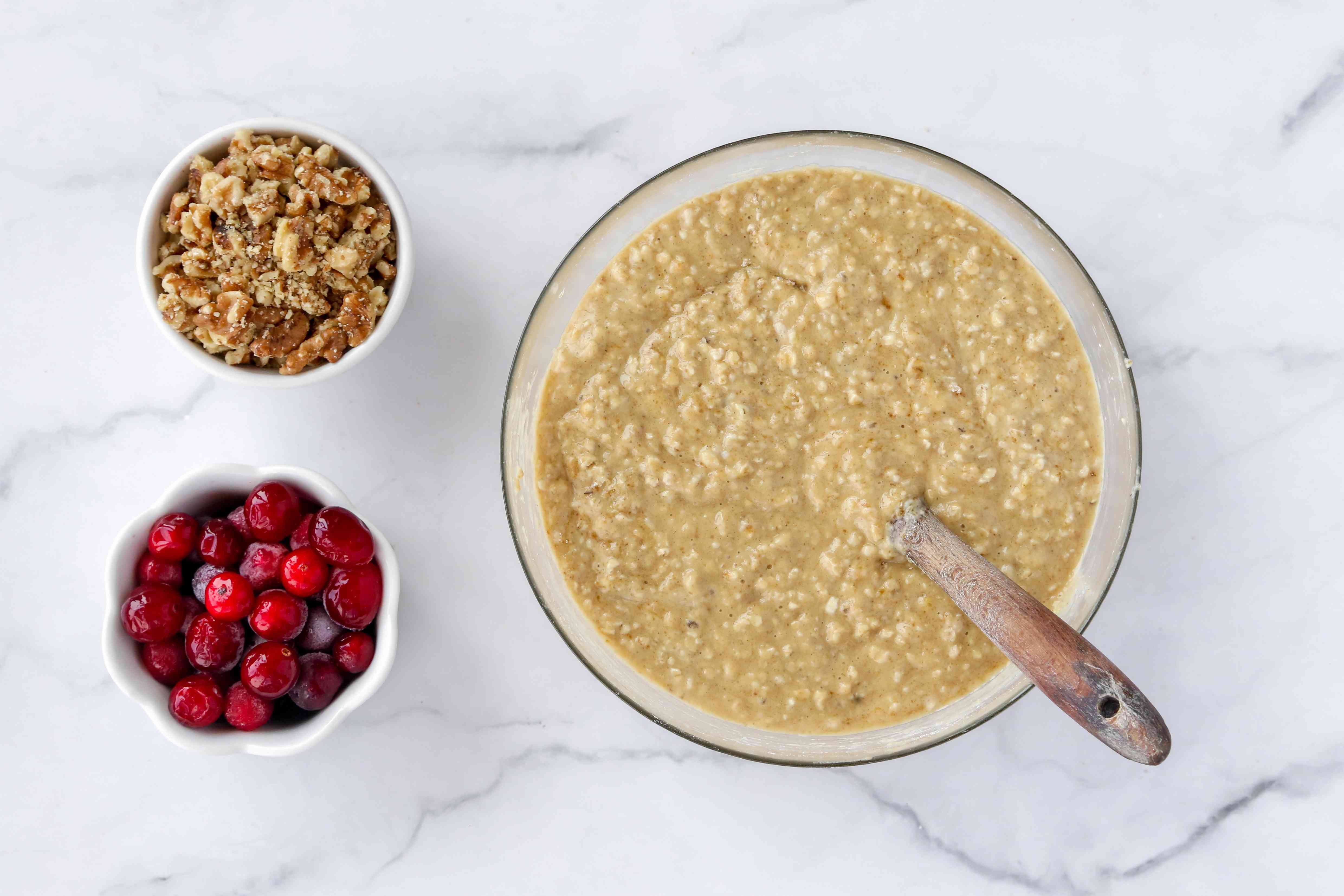 oatmeal mixture in a bowl, cranberries in a bowl, nuts in a bowl