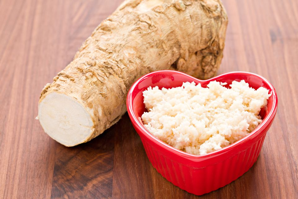 horseradish root and grated horseradish on a wooden table