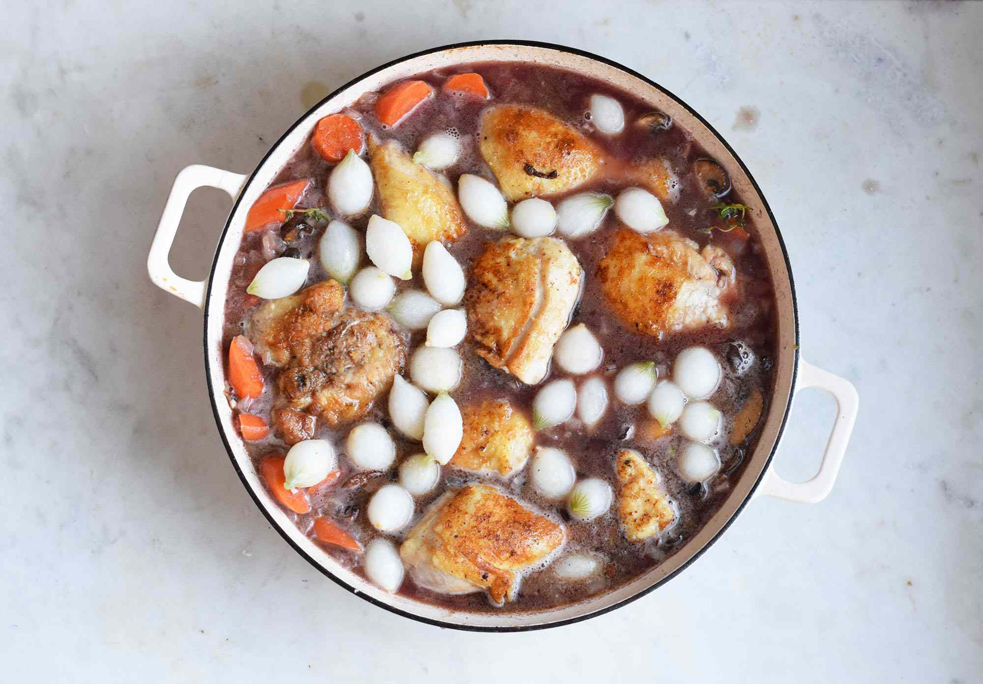 chicken and onions added to wine in a pot