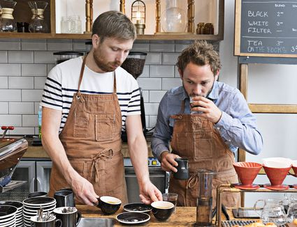 two men tasting coffee in a cafe