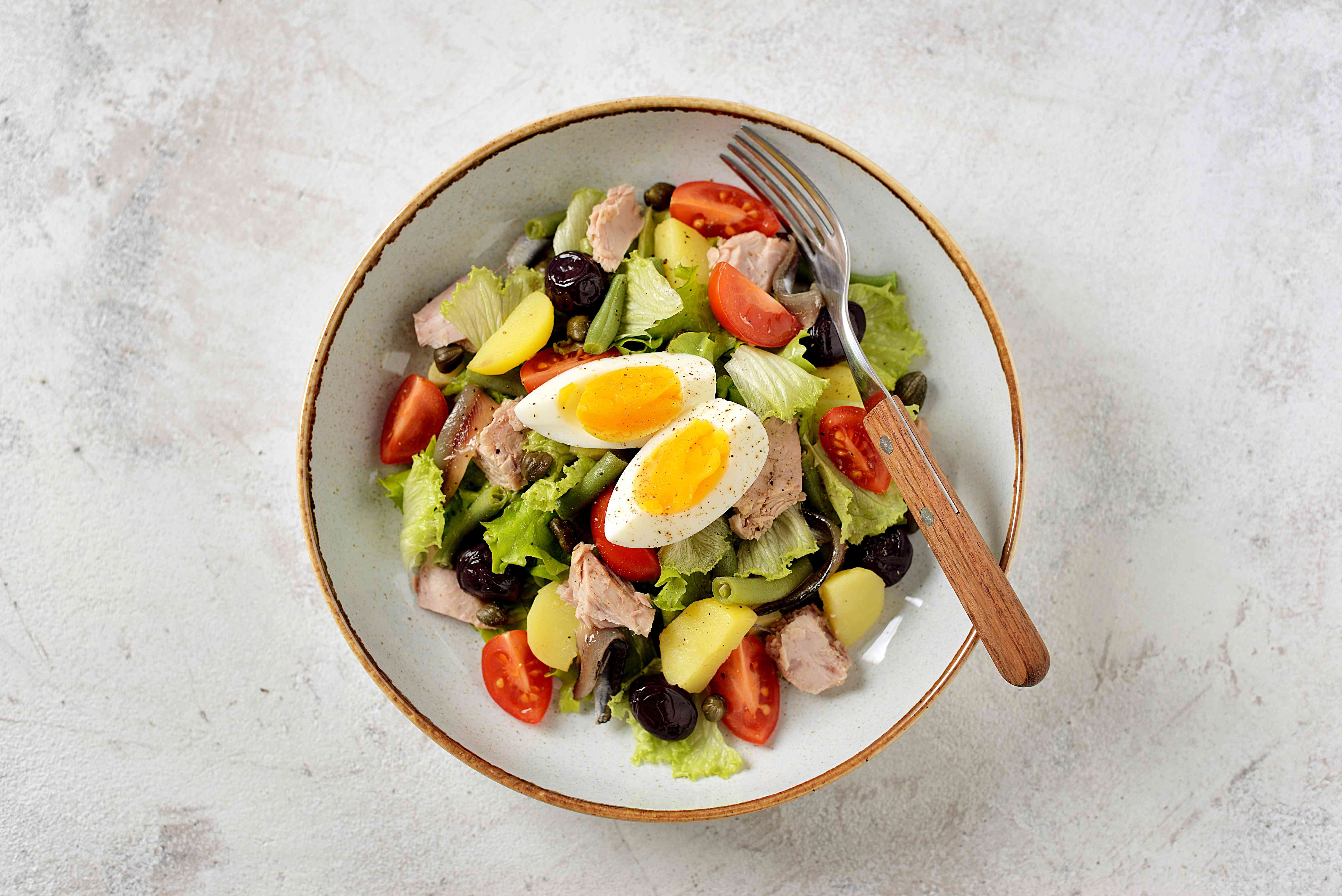 French salad Nicoise with tuna, boiled potatoes, egg, green beans, tomatoes, dried olives, lettuce and anchovies. Top View.