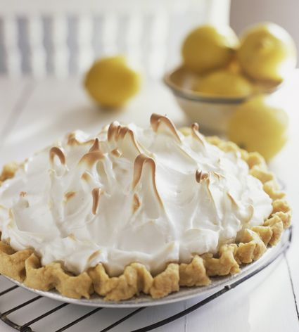 Lemon meringue pie on a cooling rack with a bowl of lemons in the background