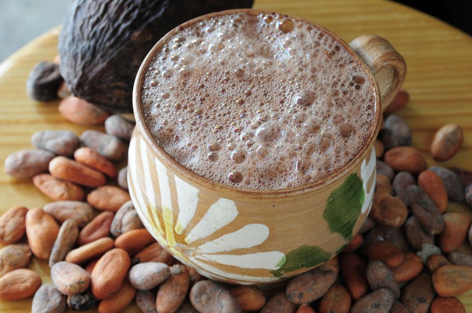 Hot chocolate in painted cup with cocoa beans and pod