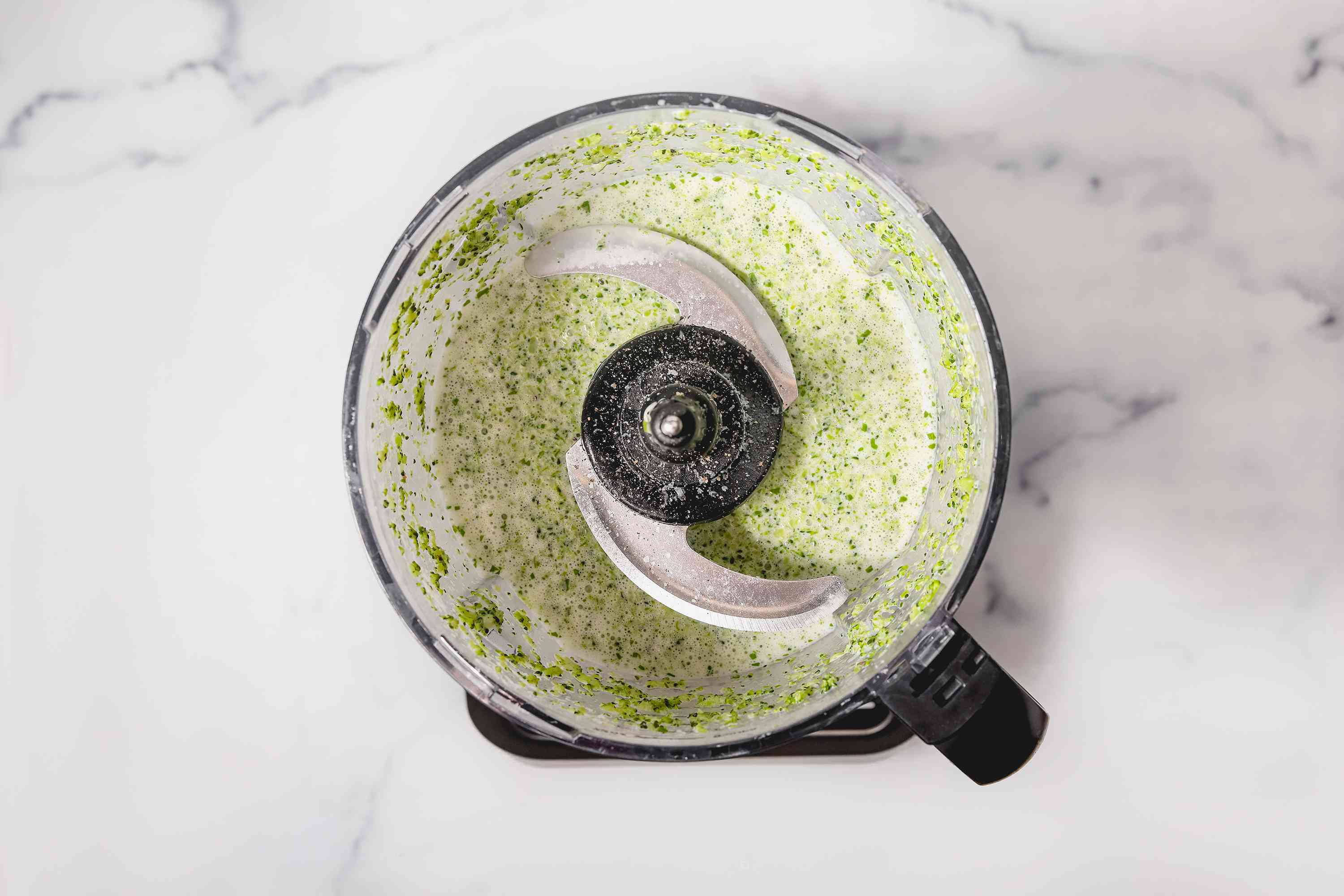 Basil, butter, cream, and Parmesan cheese added to broccoli in a food processor