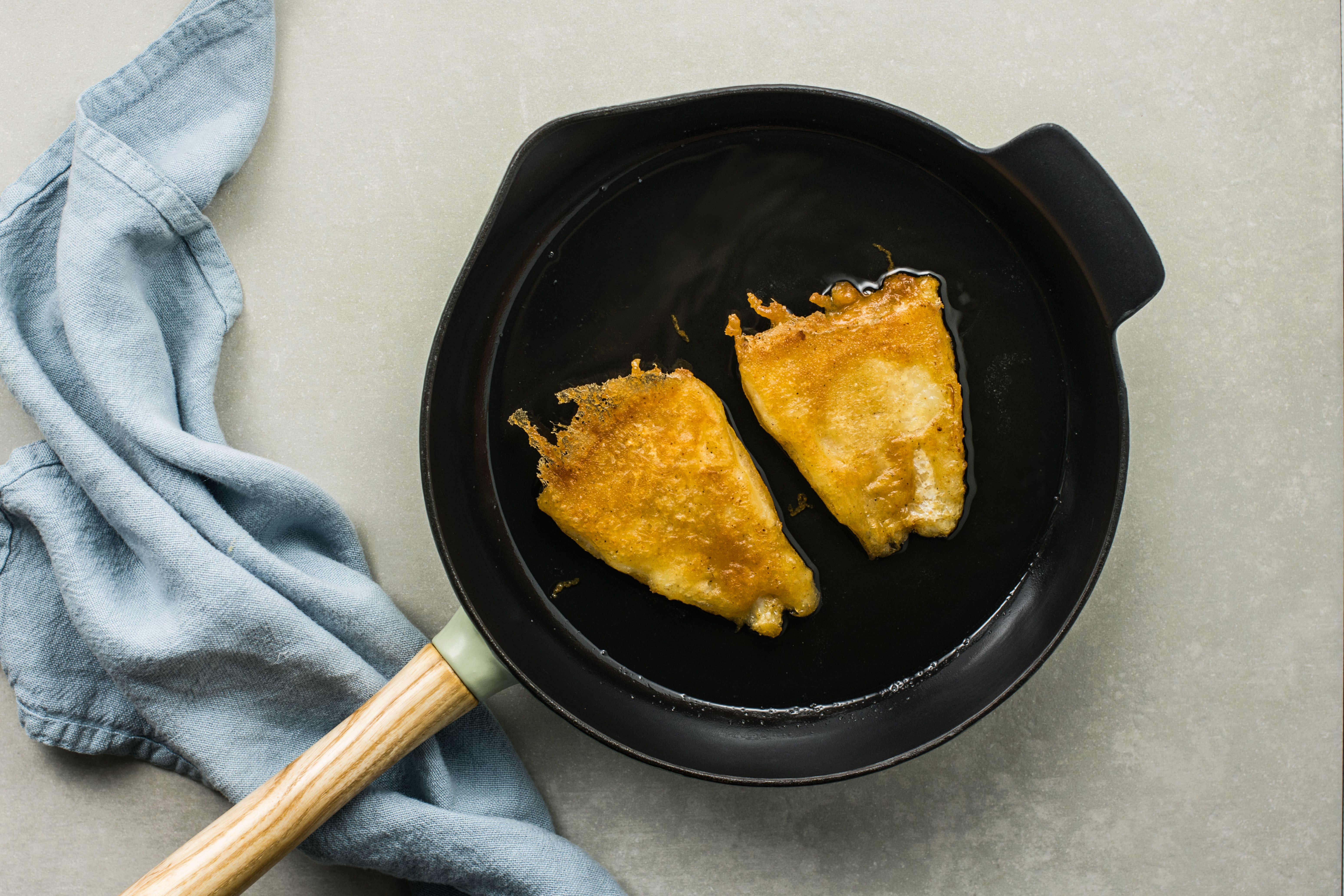 Gluten-free beer-battered fried fish cooking in the pan