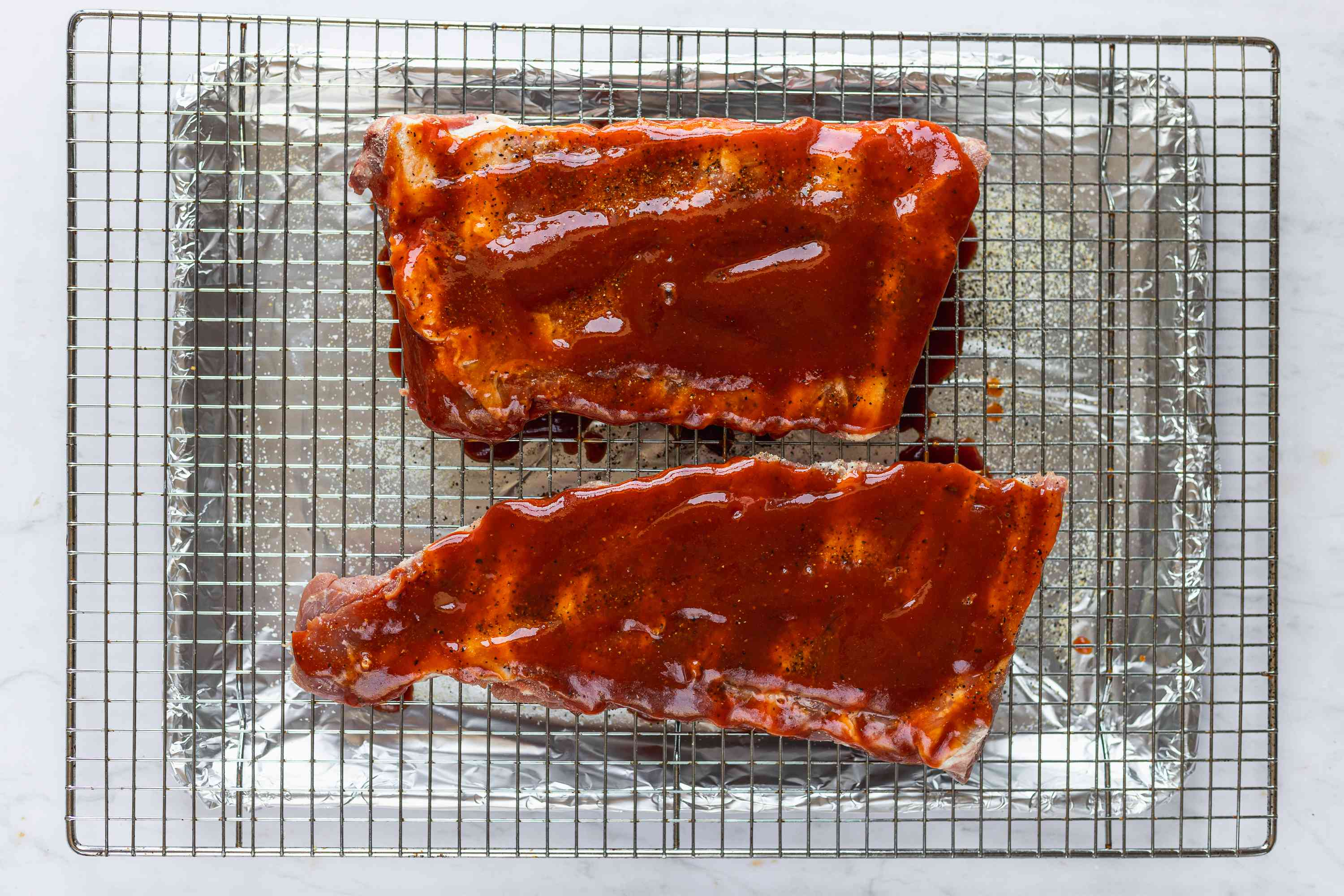 Barbecue sauced on top of the spareribs in a baking pan