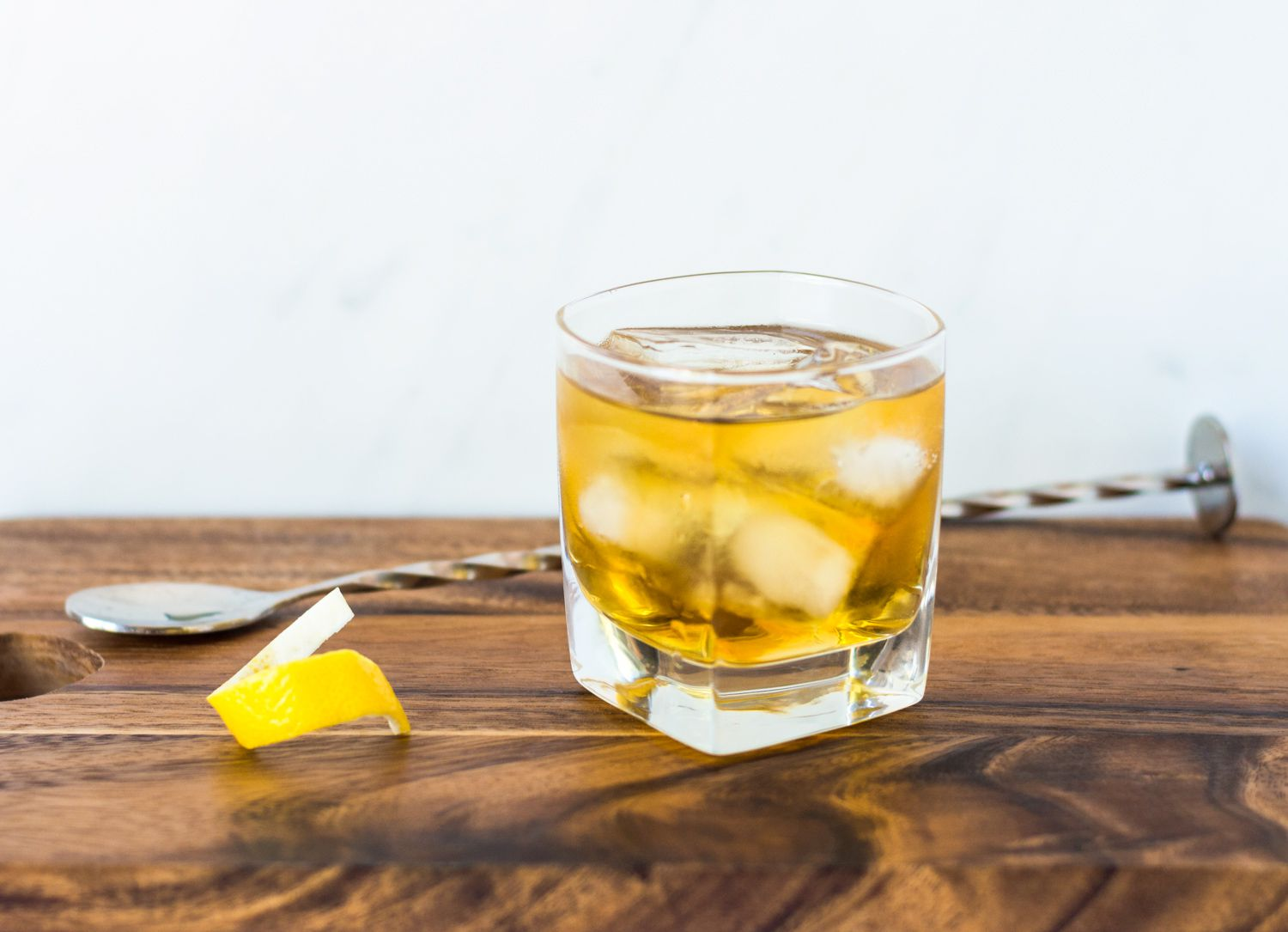Rusty nail cocktail stirred well along with lemon twist