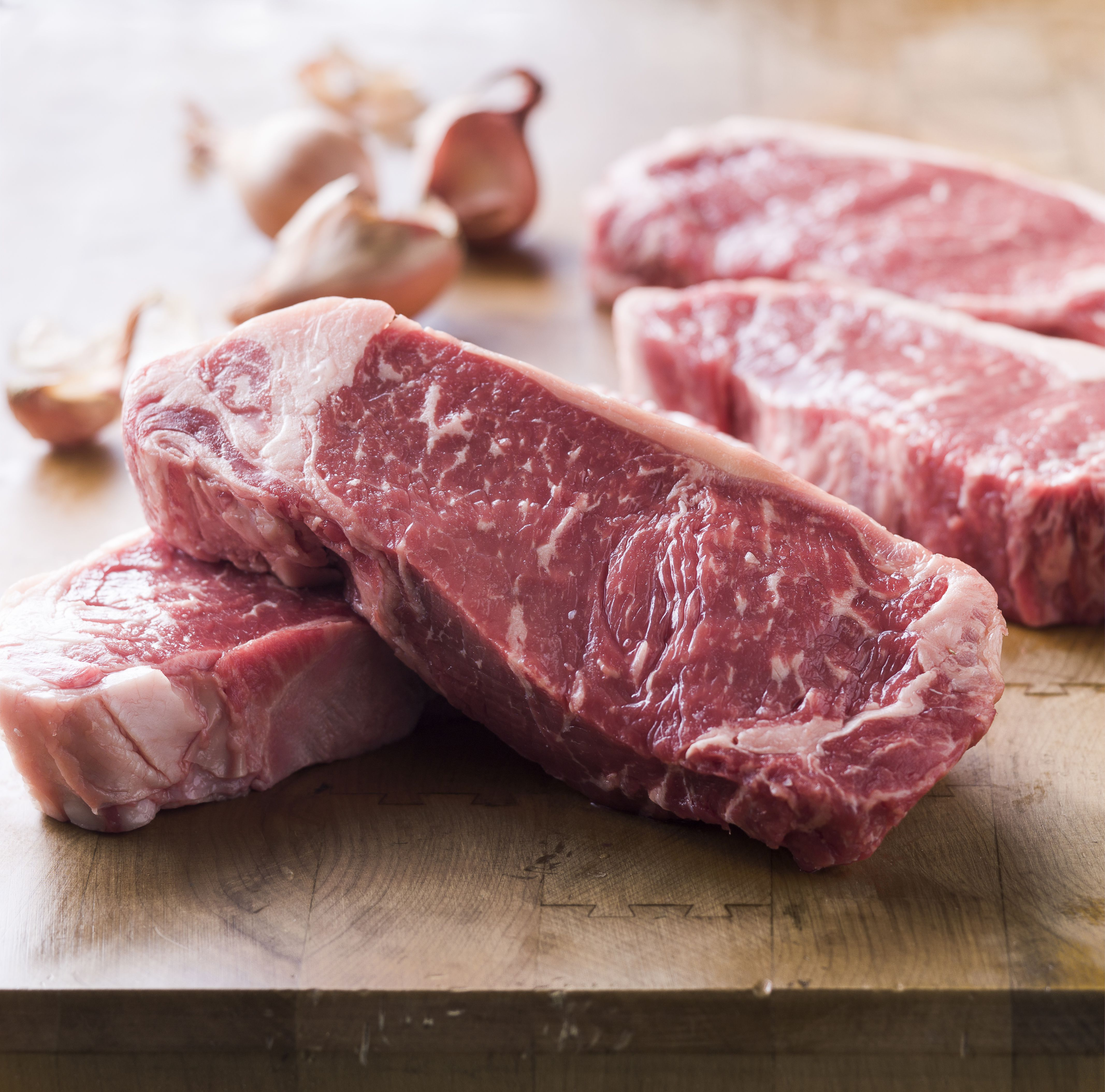 Raw steaks on wooden table