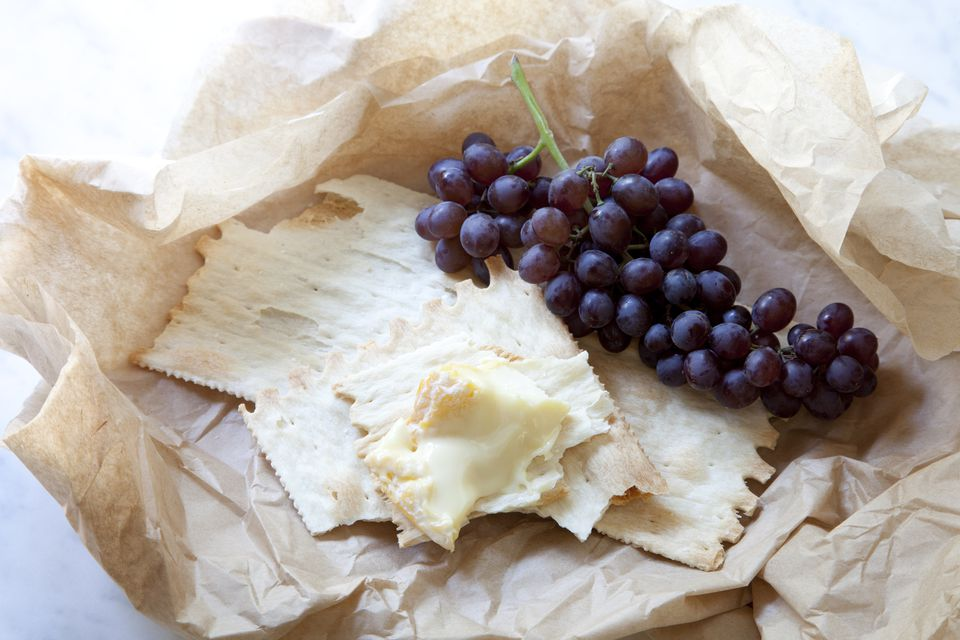 Cheese, crackers and grapes on brown paper
