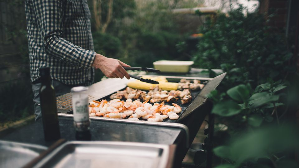 Holding tongs grilling prawns, meat and vegetables on barbecue
