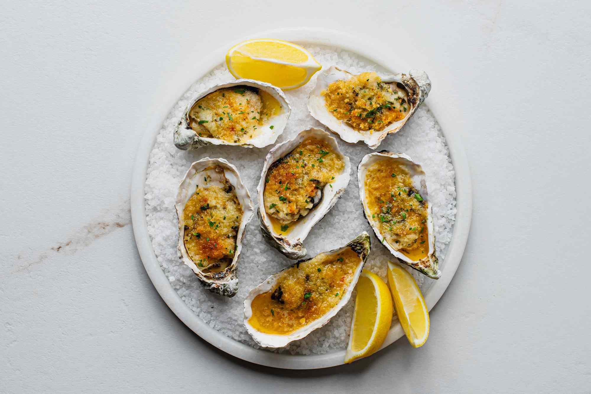 Baked oysters on a serving plate with lemon wedges