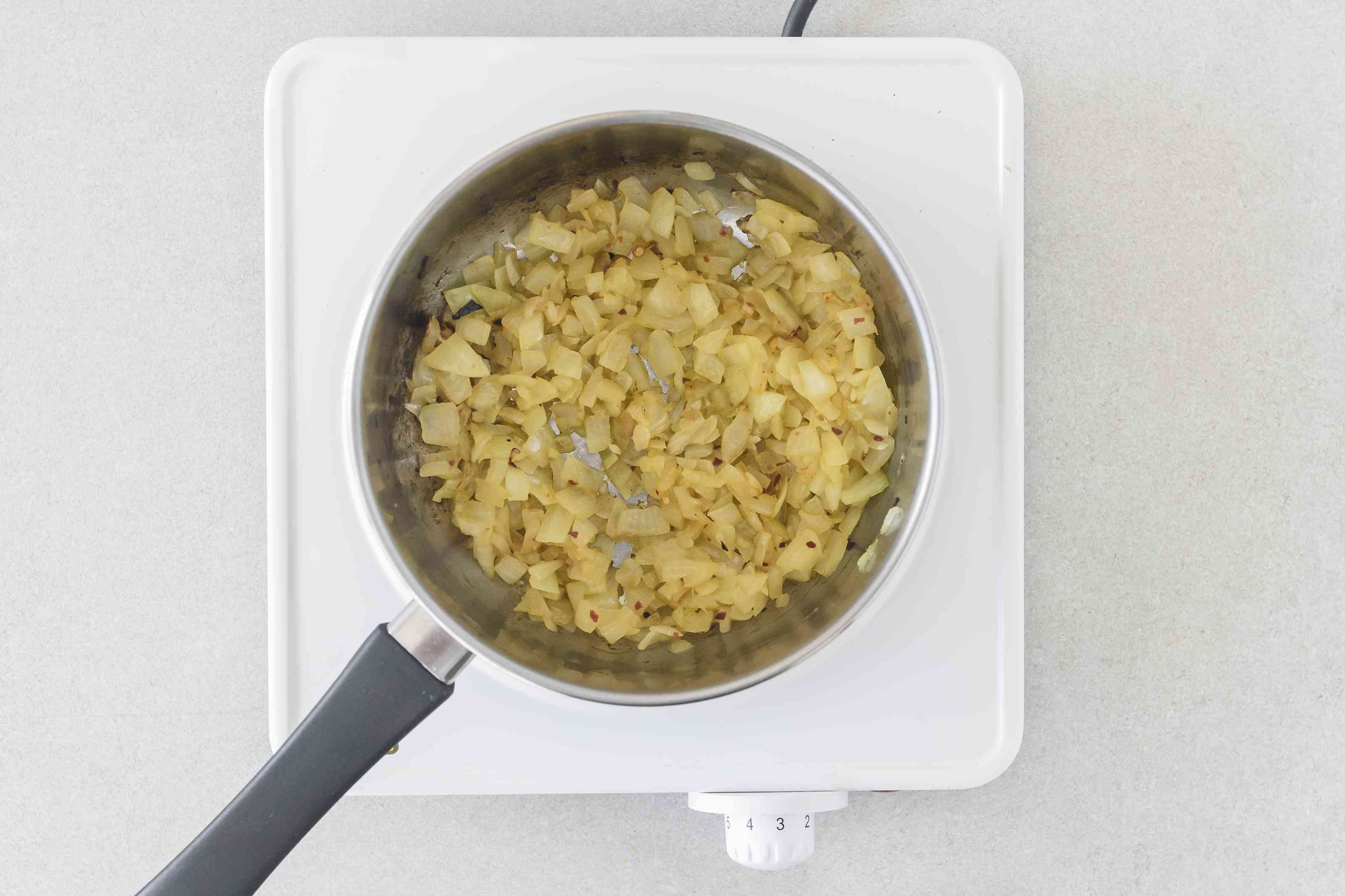 Saucepan with olive oil, onion, red pepper flakes, and salt