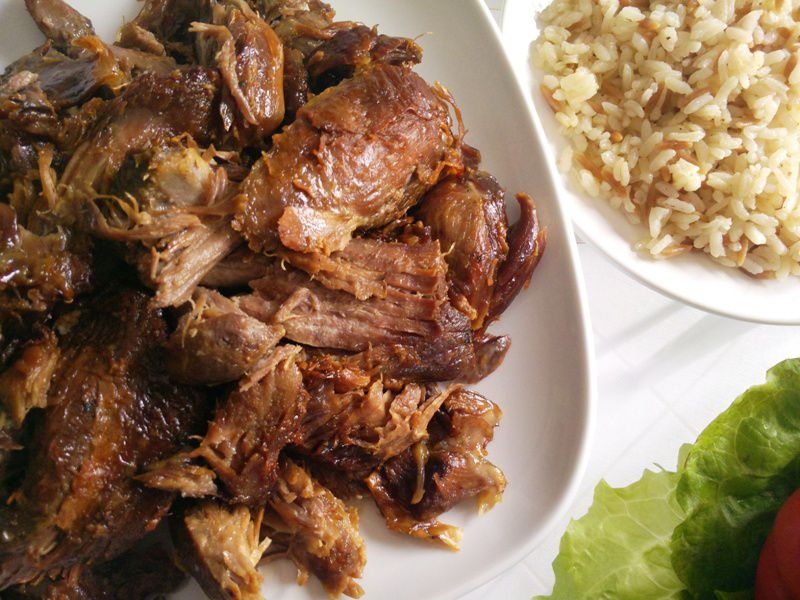 Turkish roasted lamb (kuzu tandır) on plate, rice on a second plate