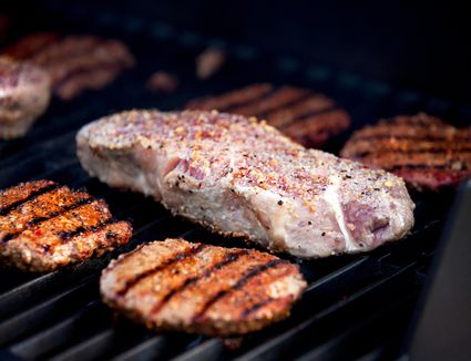 Hamburgers and strip steaks cooking on gas grill