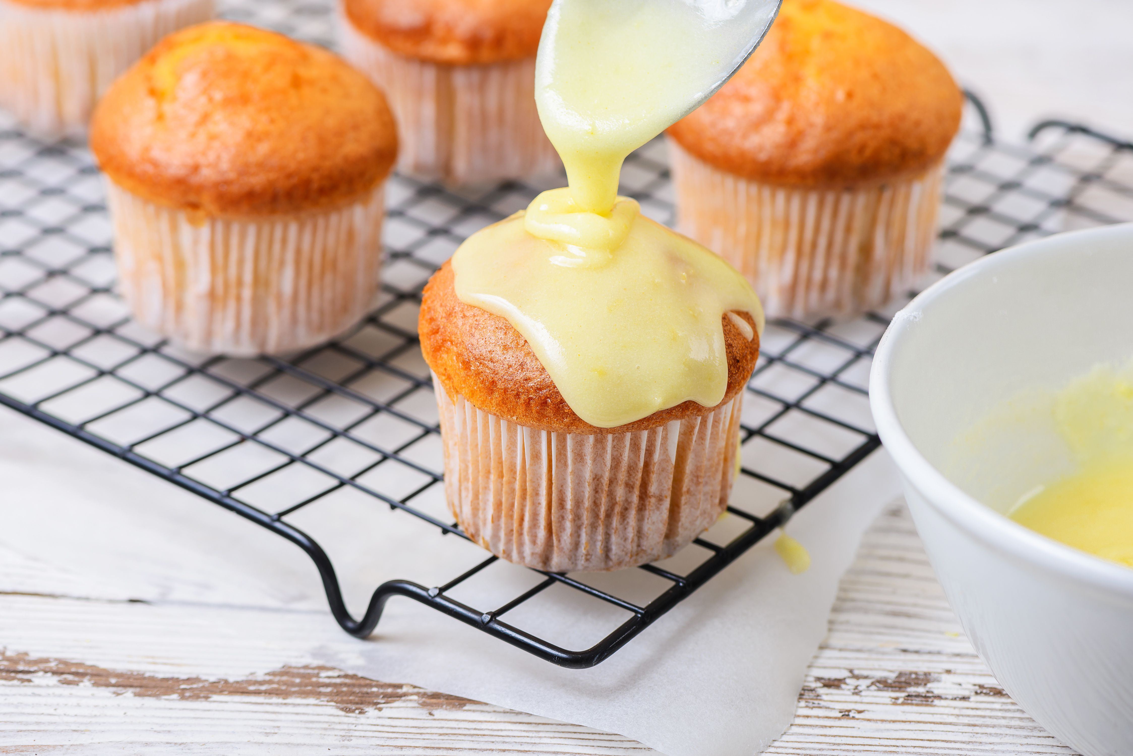 Lemon glaze icing drizzled on top of a cupcake