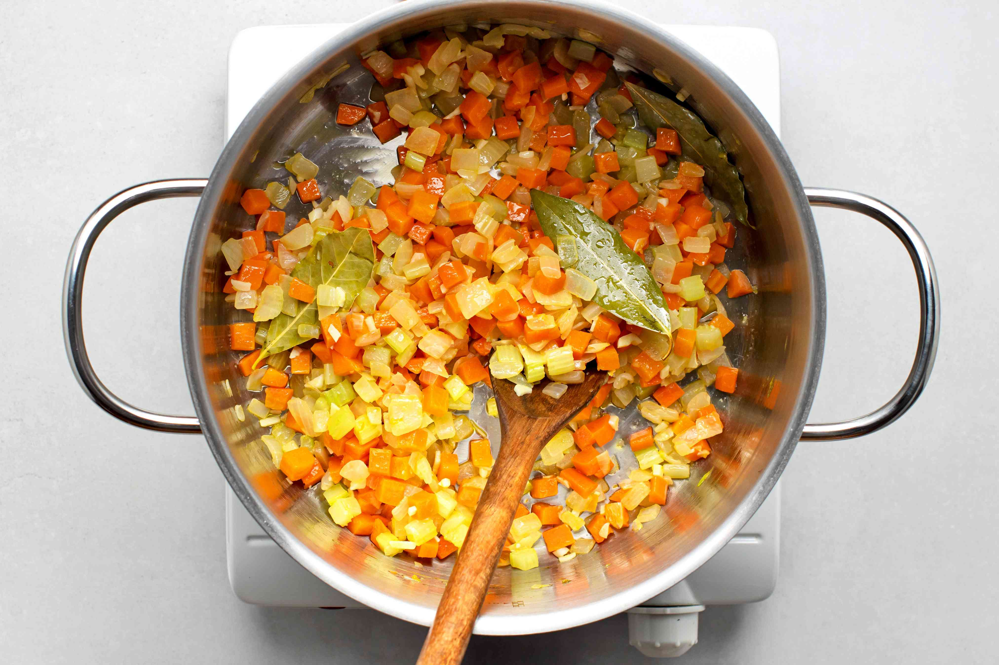 Add the onion, celery, carrots, garlic, and bay leaves and saute in the pot