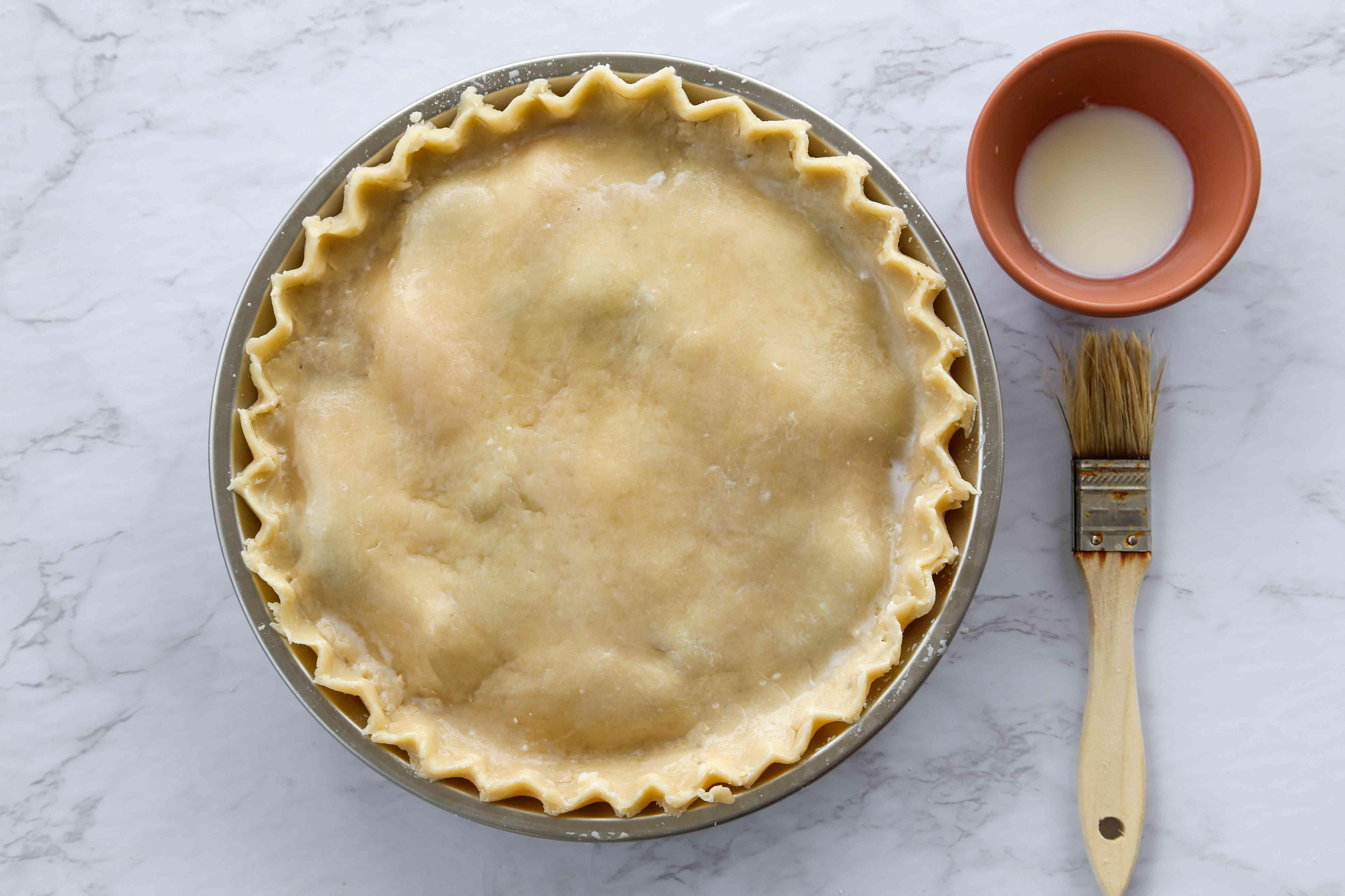 Brush the pie top with milk
