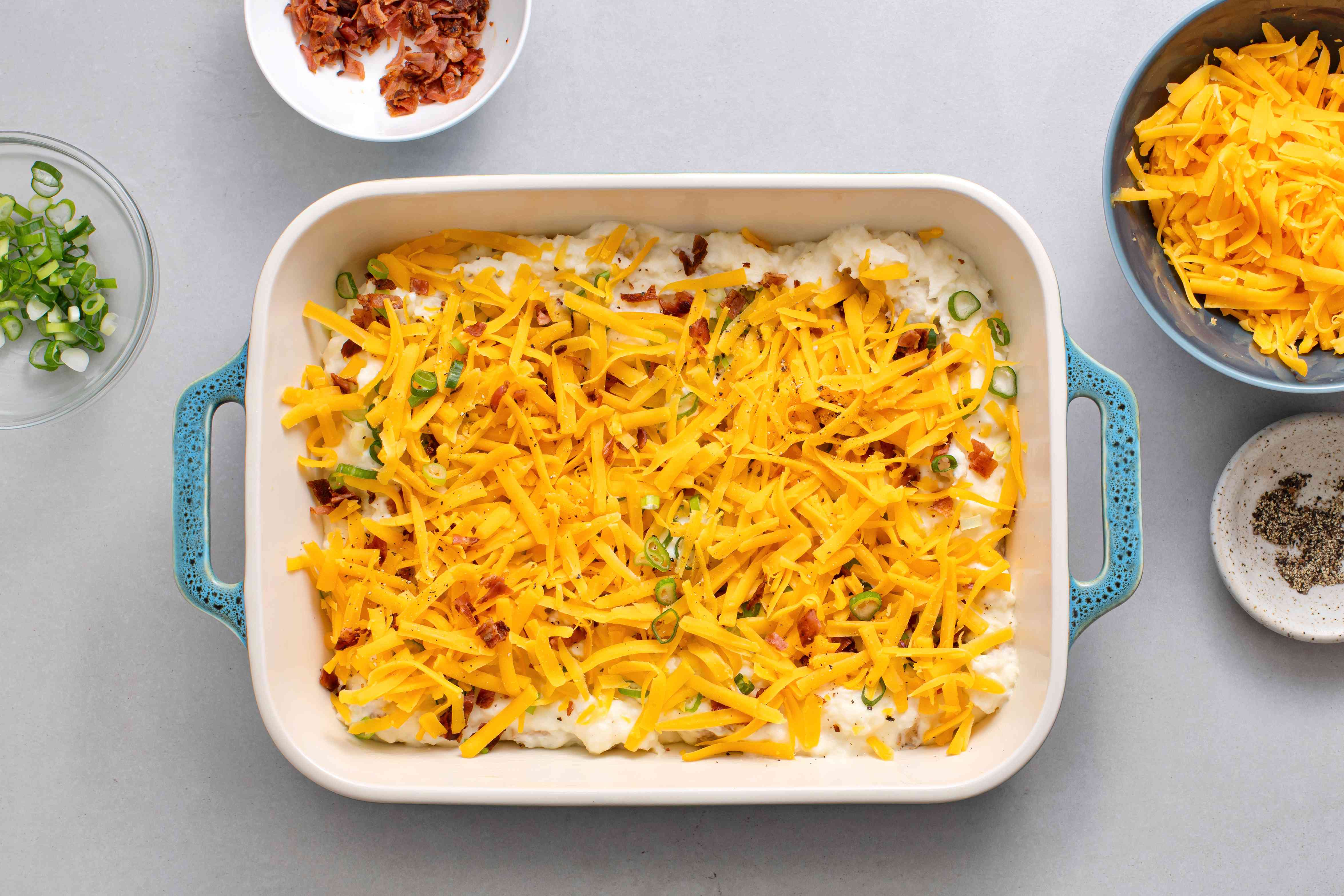 bacon, scallions, and cheddar cheese in a baking dish