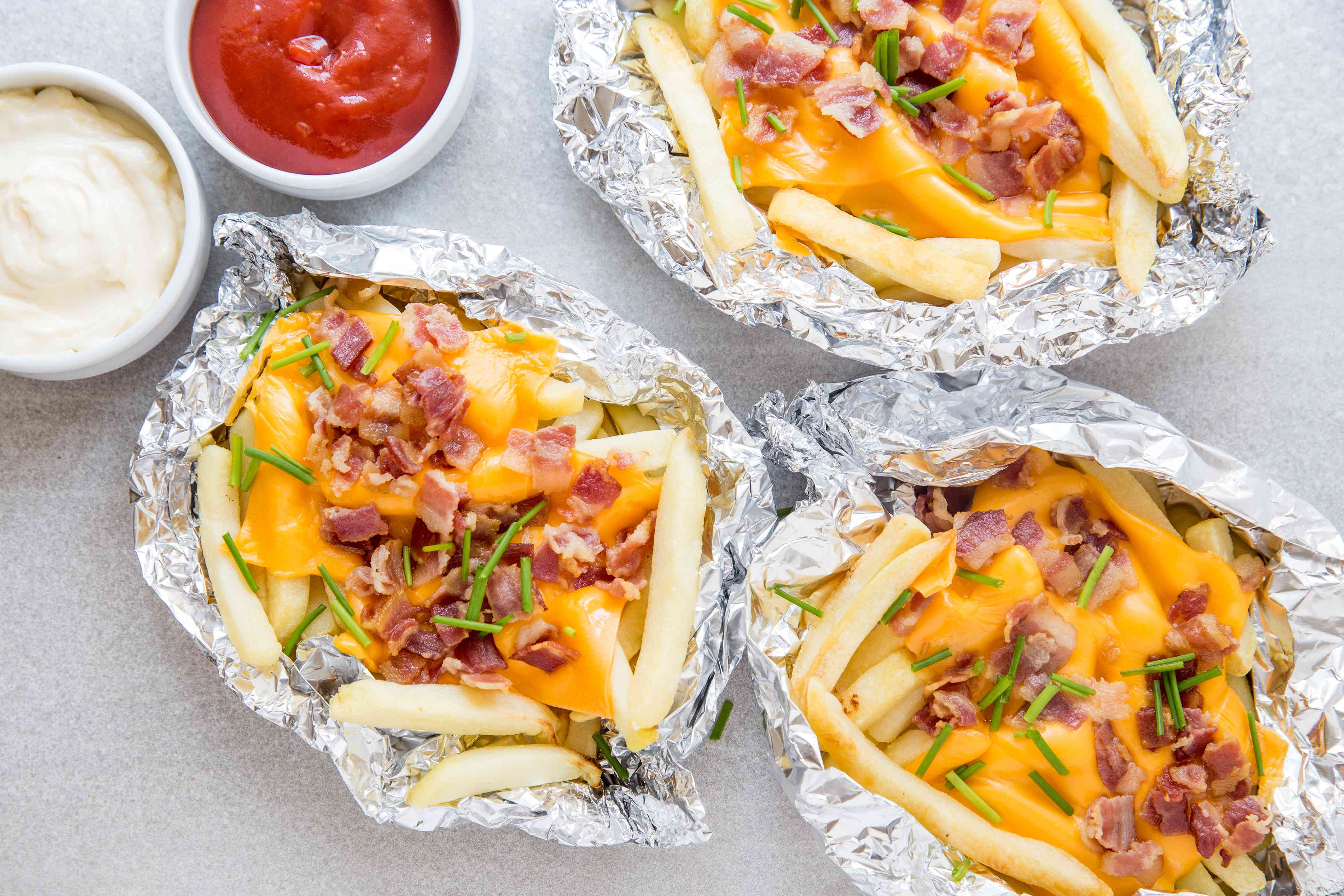 French Fries on the Grill With Cheese and Bacon in aluminum foil boats