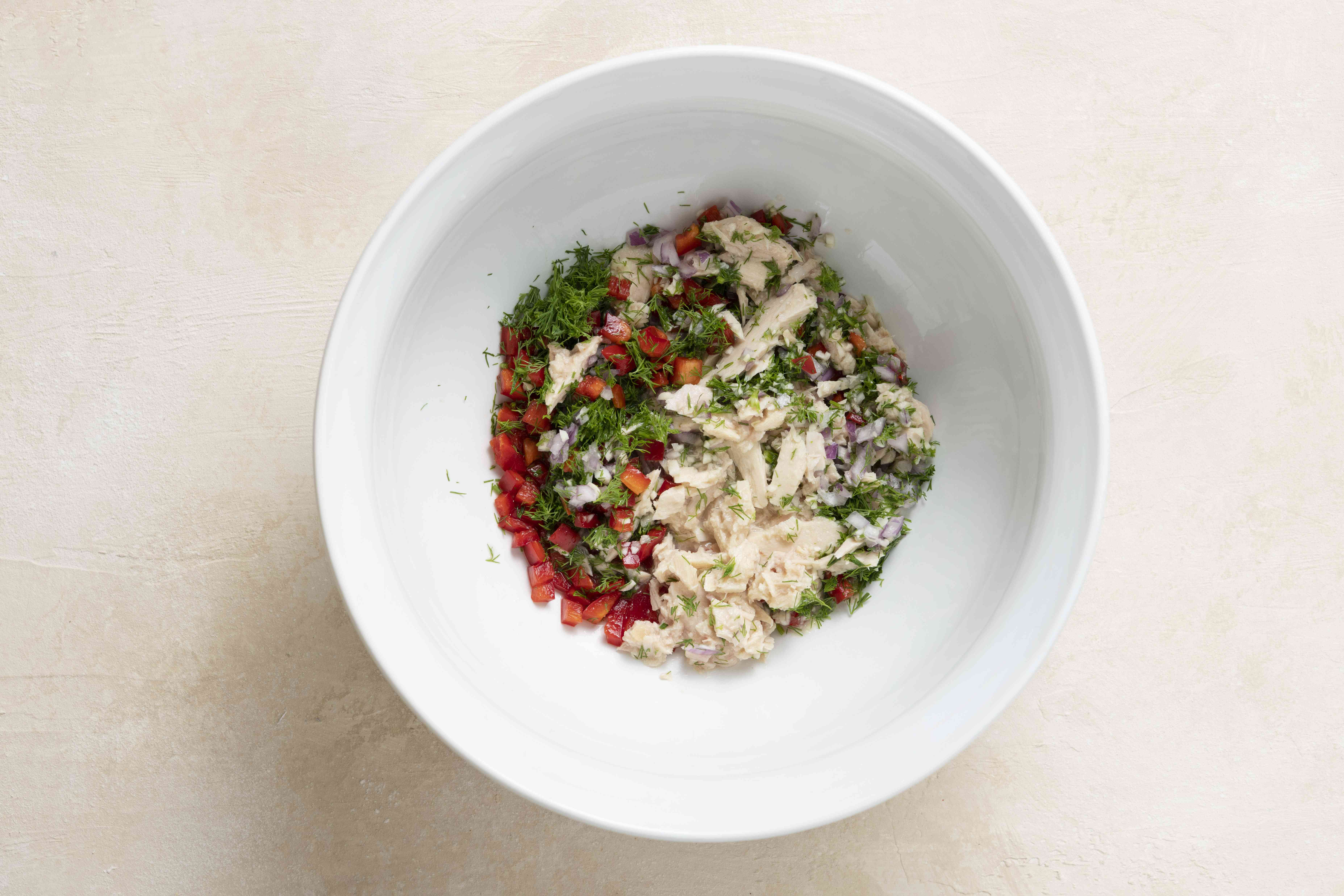 combine the tuna, finely chopped onion, minced garlic, bell pepper, dill, and lemon juice in a bowl