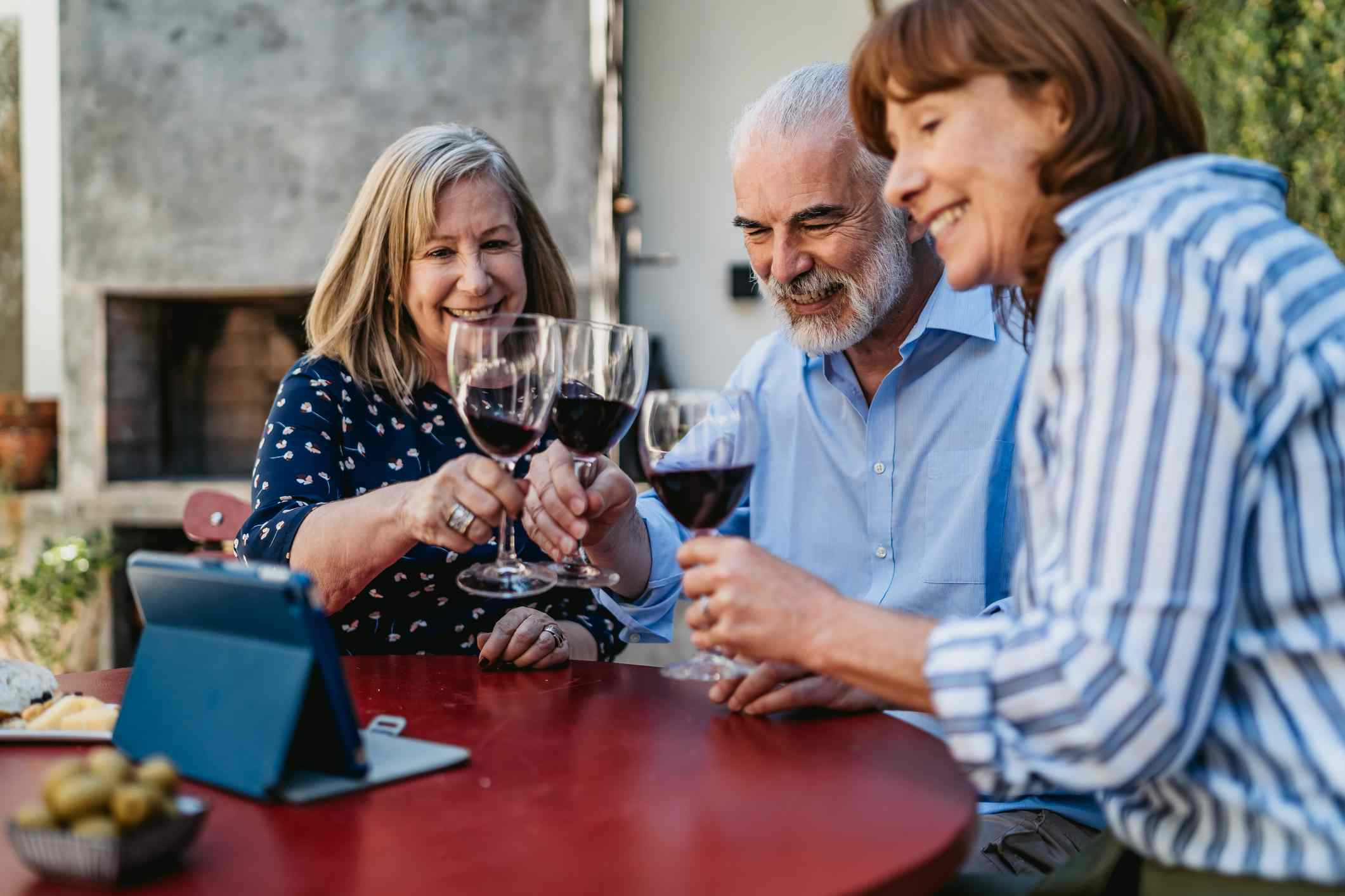 friends toasting with a glass of wine while watching video on a tablet