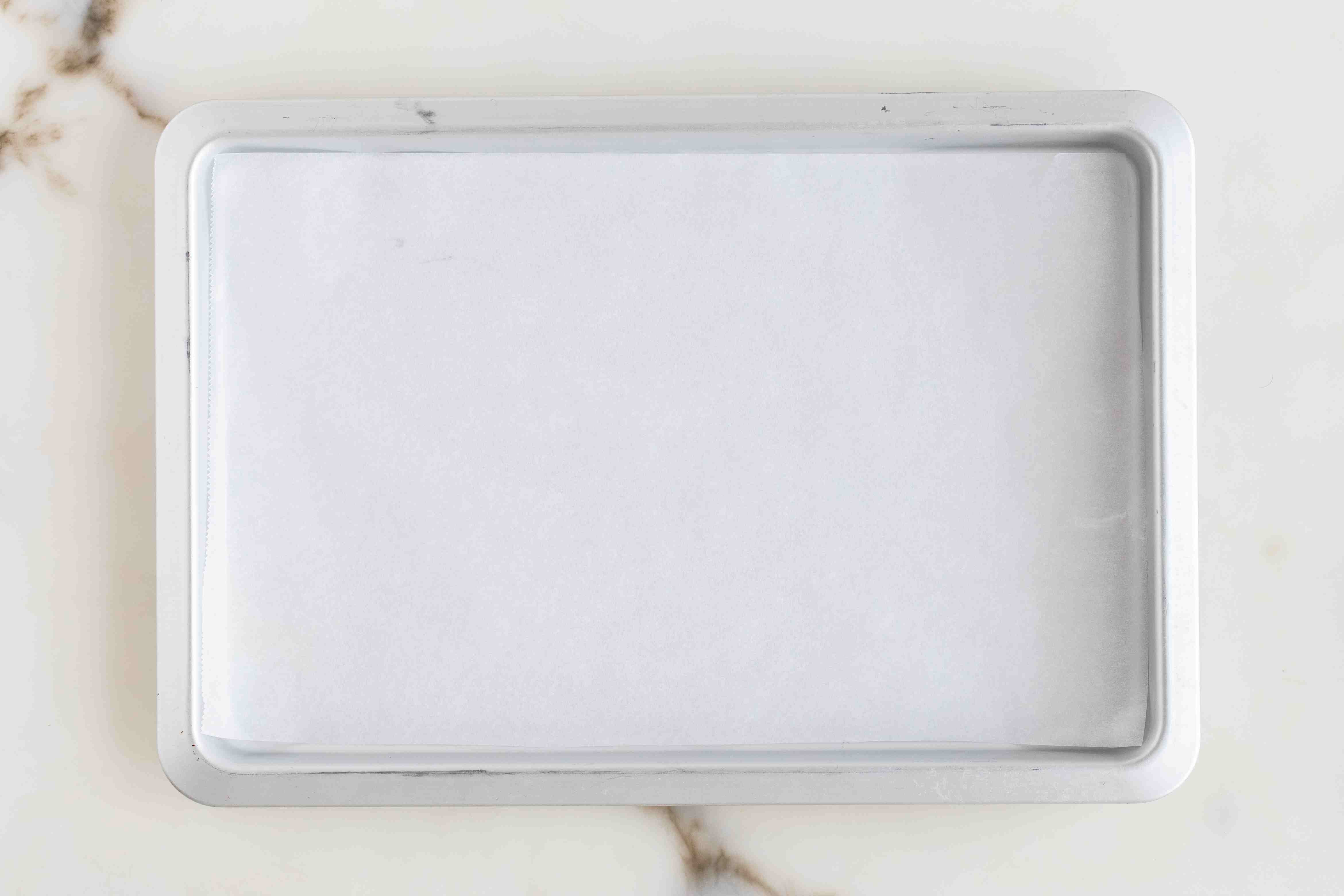 Line baking sheet with parchment