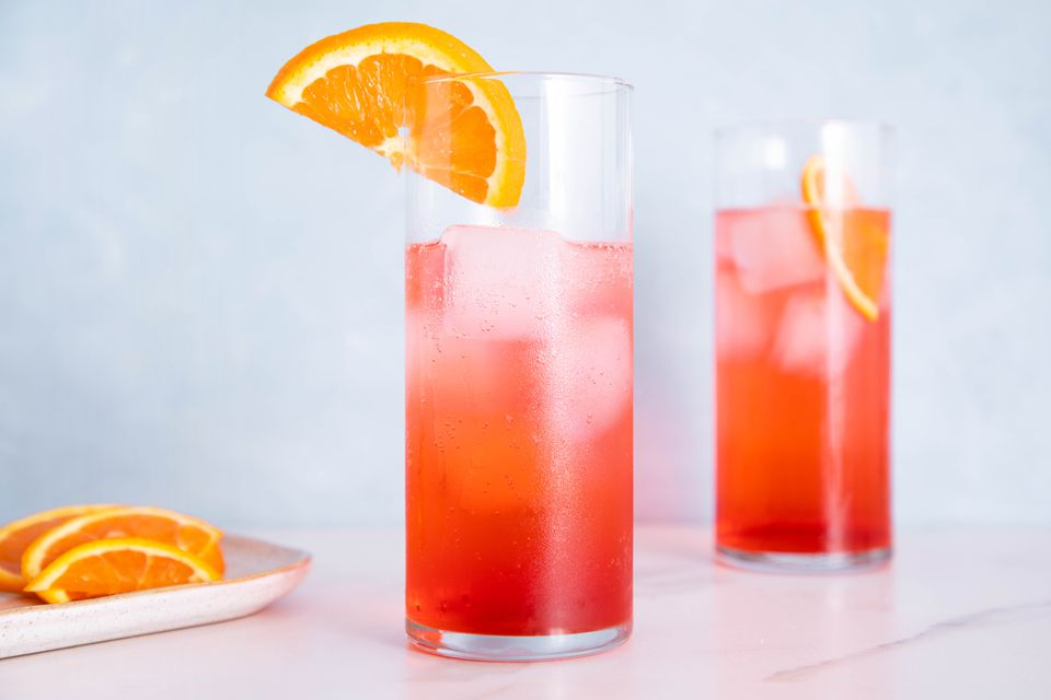 Two Campari and soda cocktails in highball glasses garnished with orange