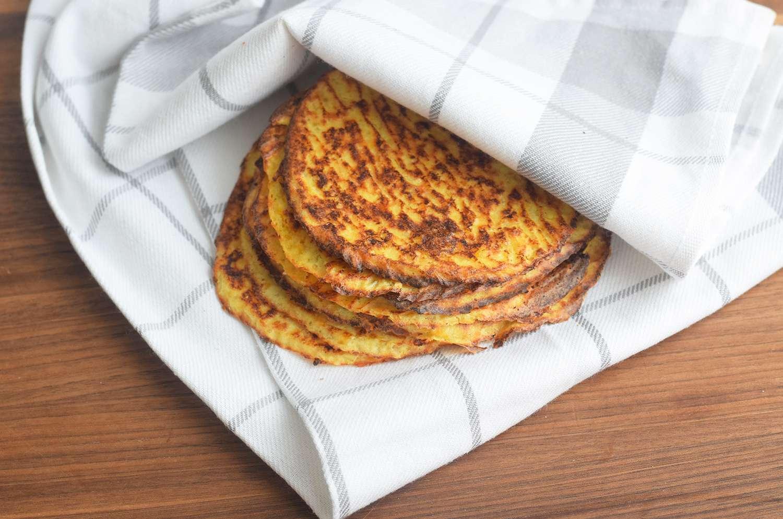 Cauliflower tortillas in a tea towel on a cutting board