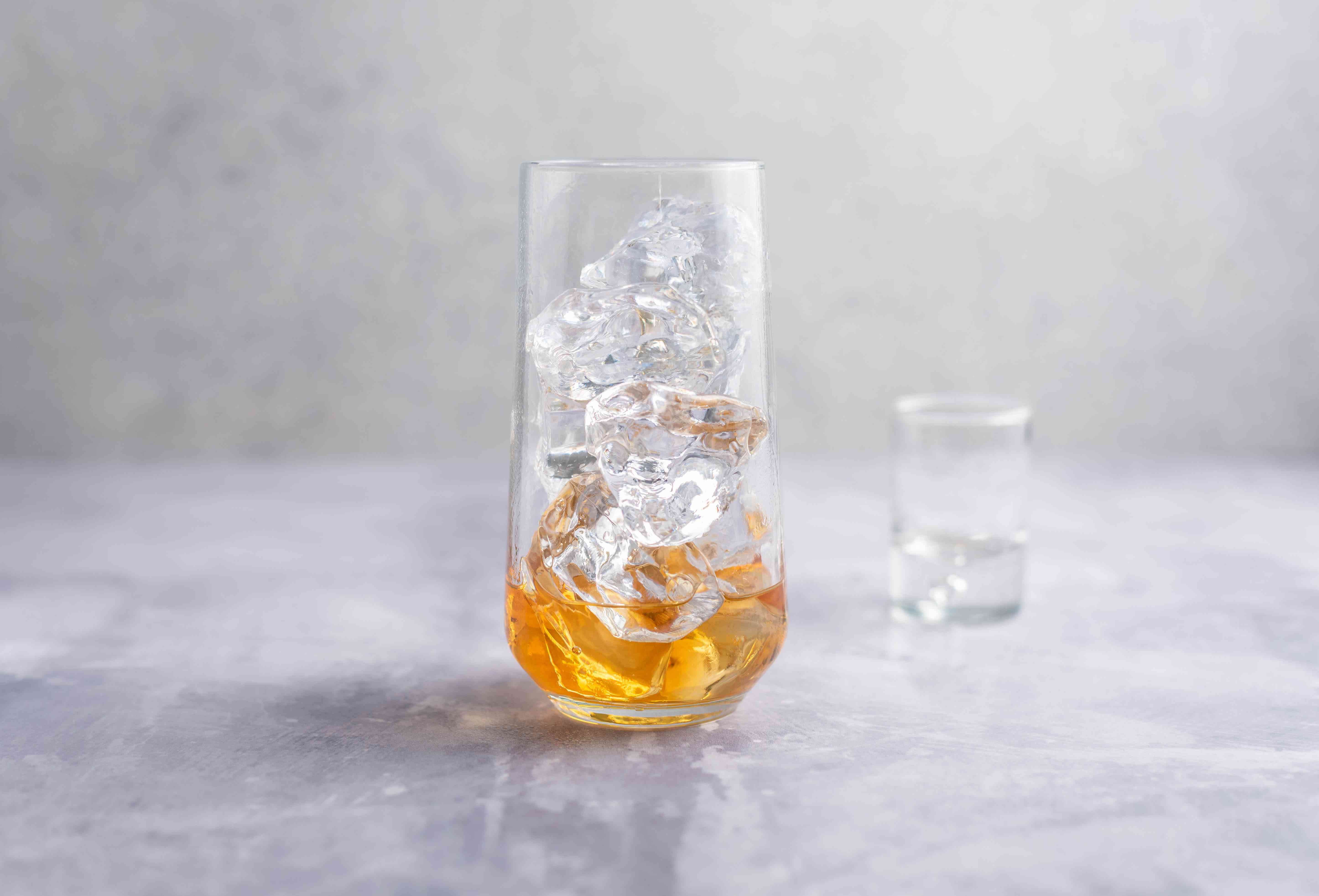 Whiskey poured into glass with ice