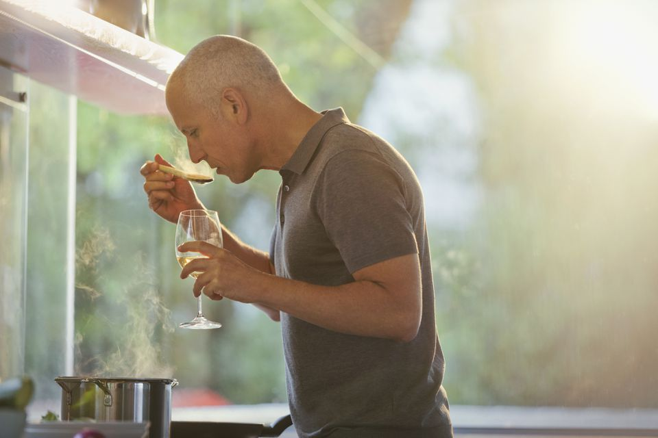 Man drinking white wine and cooking at stove in kitchen