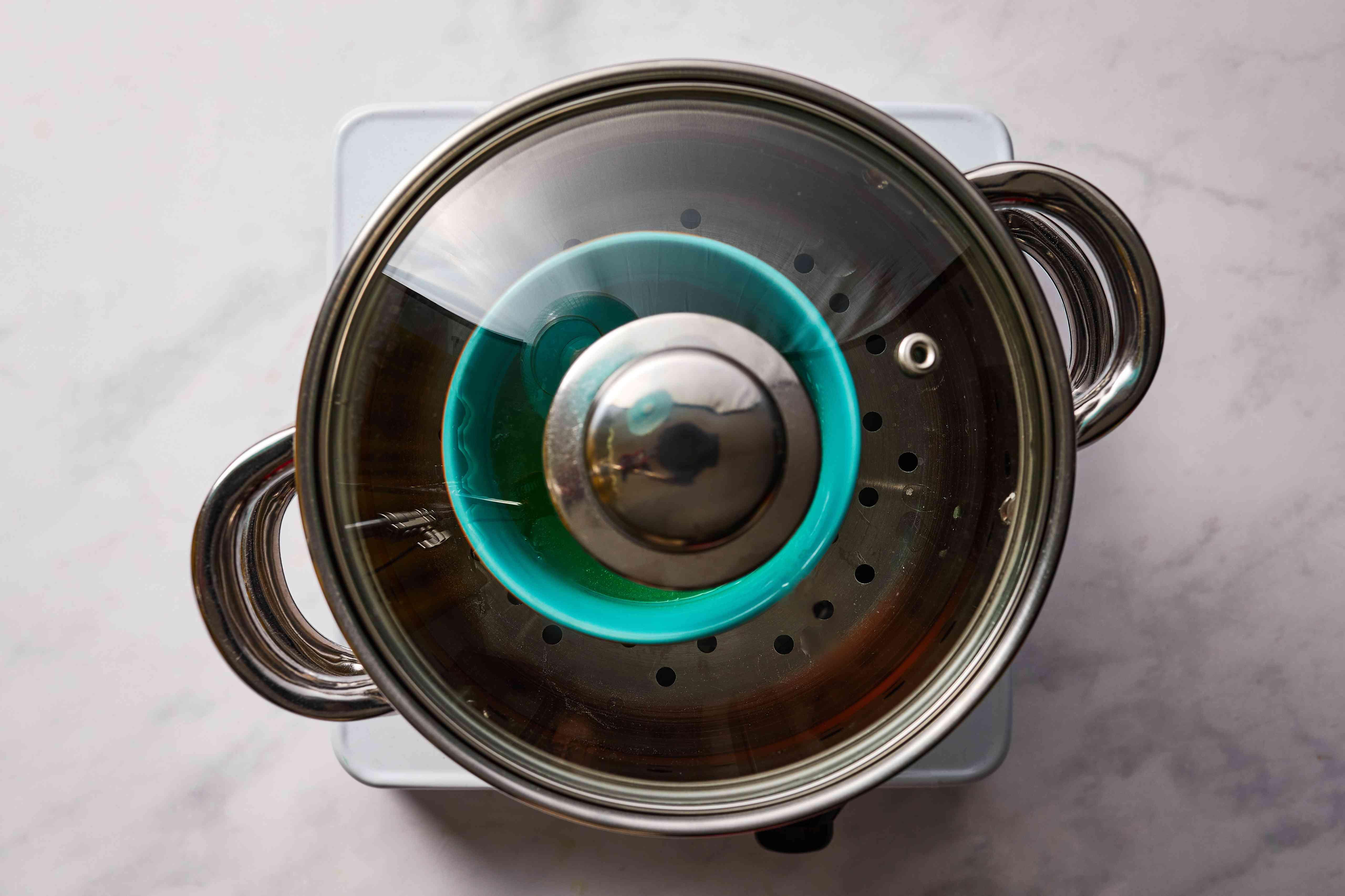 green mixture in a ramekin in a steamer