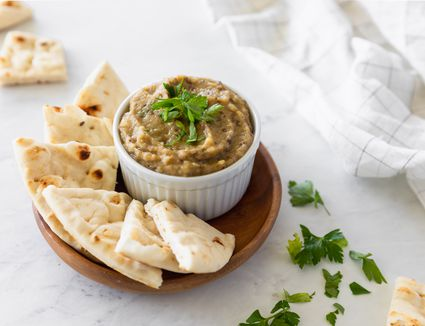 Baba ganoush in a bowl with pita bread wedges
