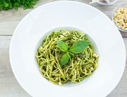 Homemade basil pasta with green pesto in bowl