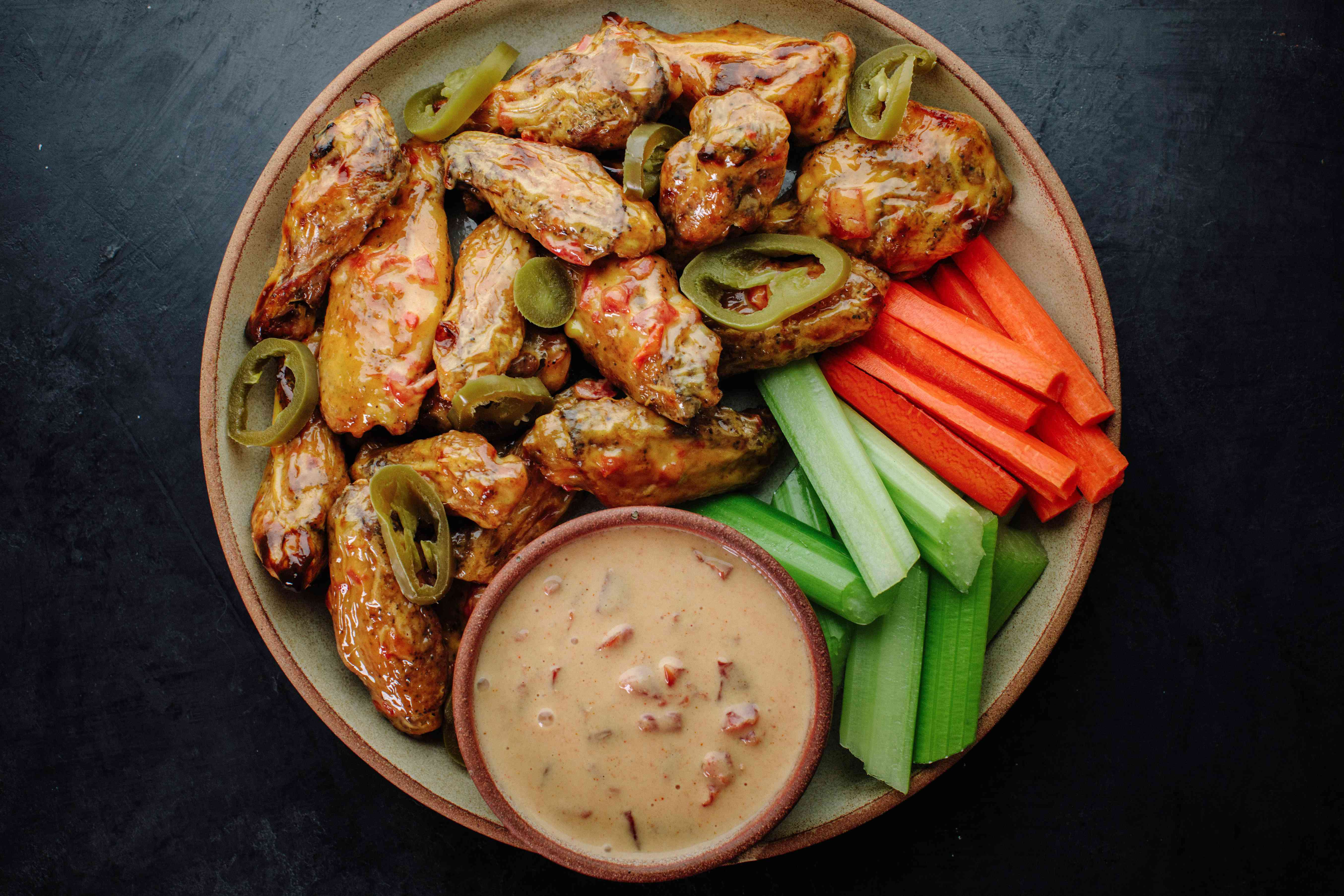 Queso Wings with pickled jalapenos, extra queso dip, carrots, celery