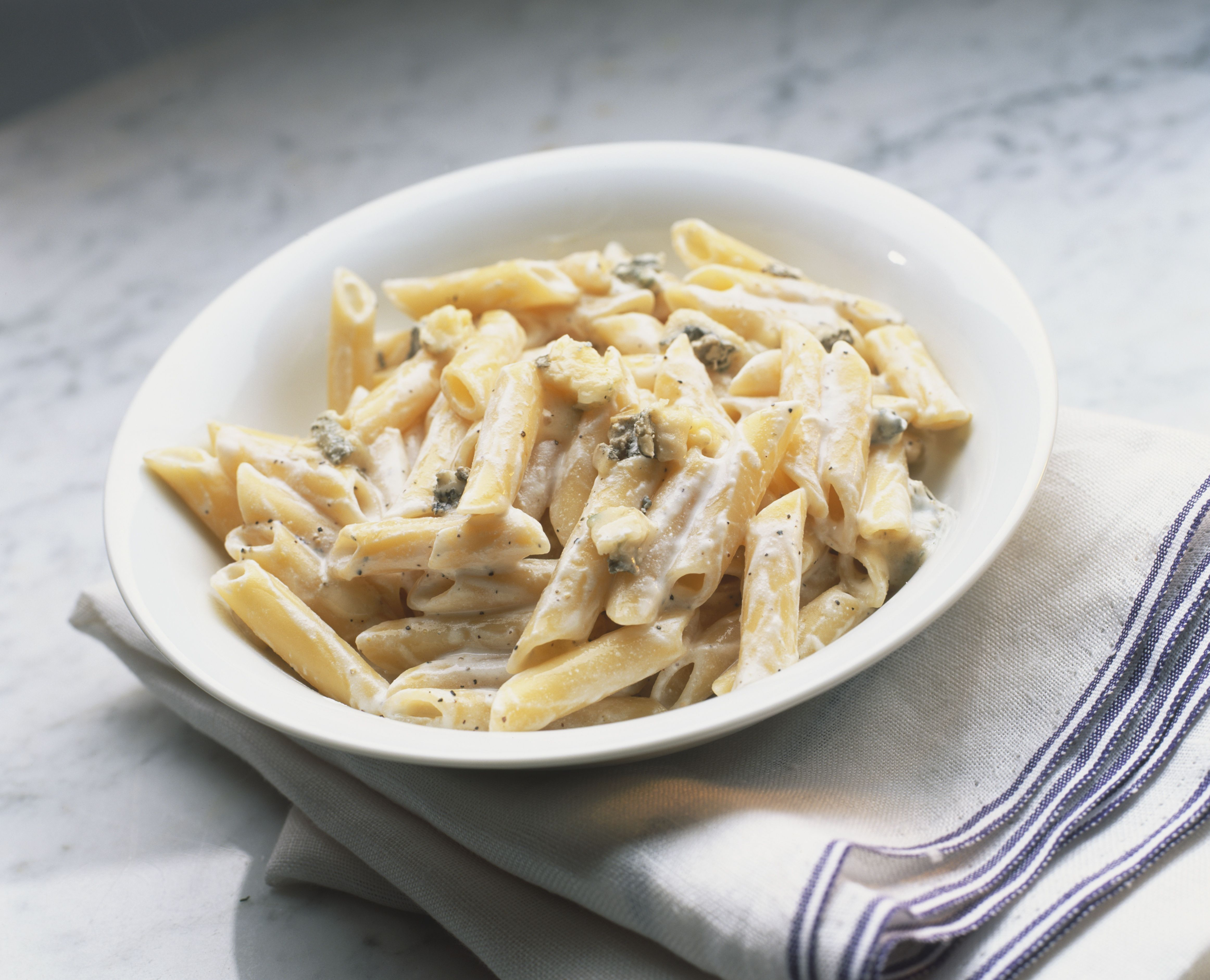 Penne pasta, thick creamy gorgonzola sauce, in white ceramic bowl, tilted angle.